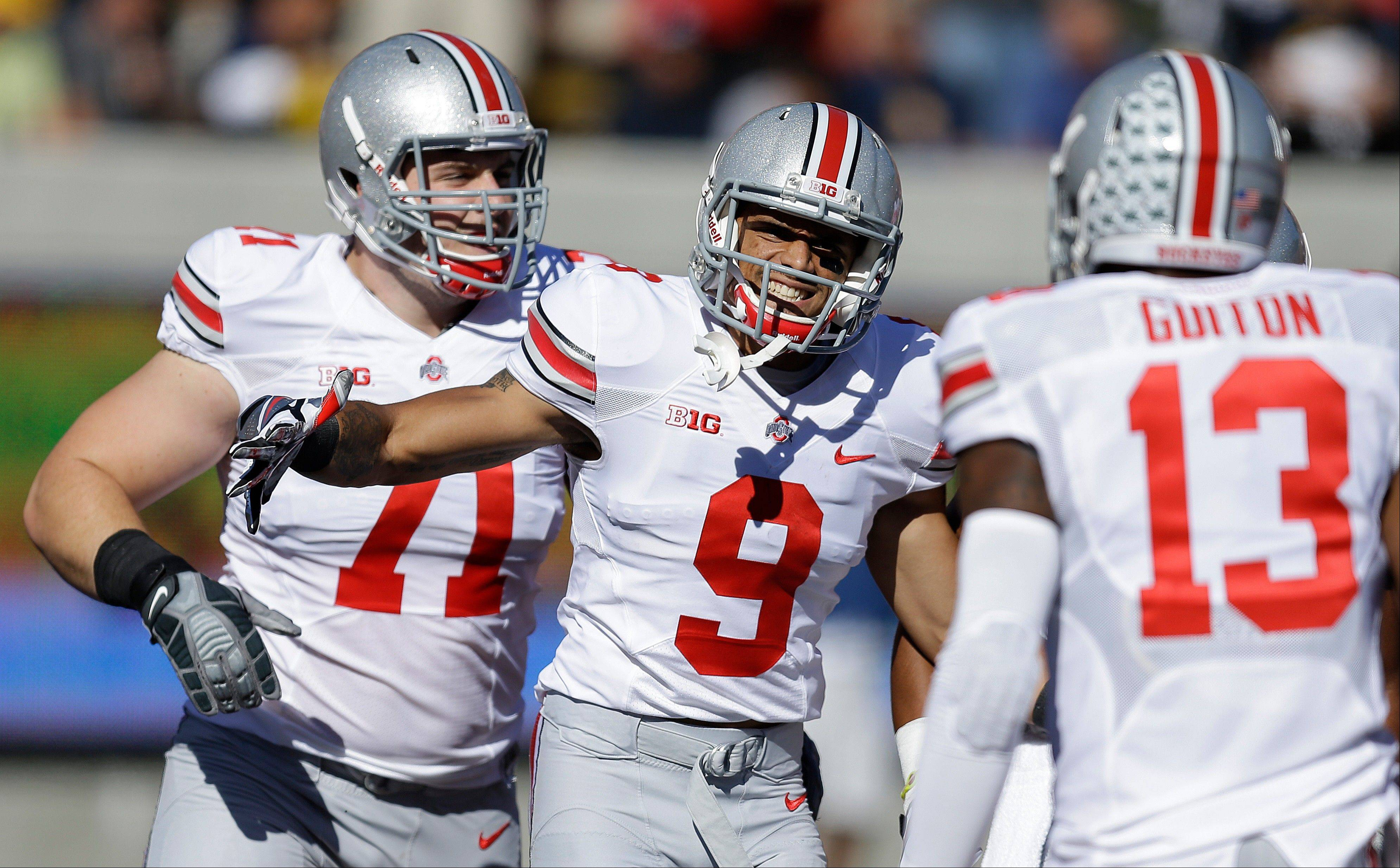 Ohio State's Devin Smith (9) celebrates with quarterback Kenny Guiton (13) and Corey Linsley (71) after Smith scored a touchdown against California during the first quarter of an NCAA college football game, Saturday, Sept. 14, 2013, in Berkeley, Calif.