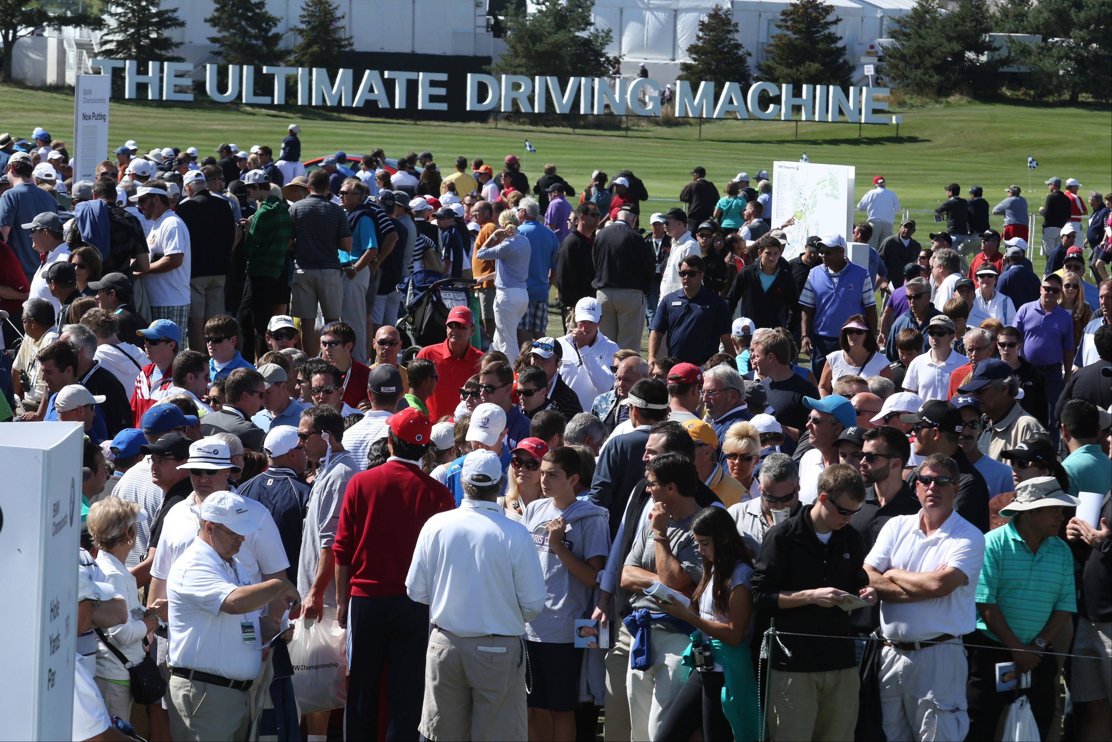 Fans travel between the driving range and the first tee during the third-round of the BMW Championship at Conway Farms Golf Club in Lake Forest on Friday.
