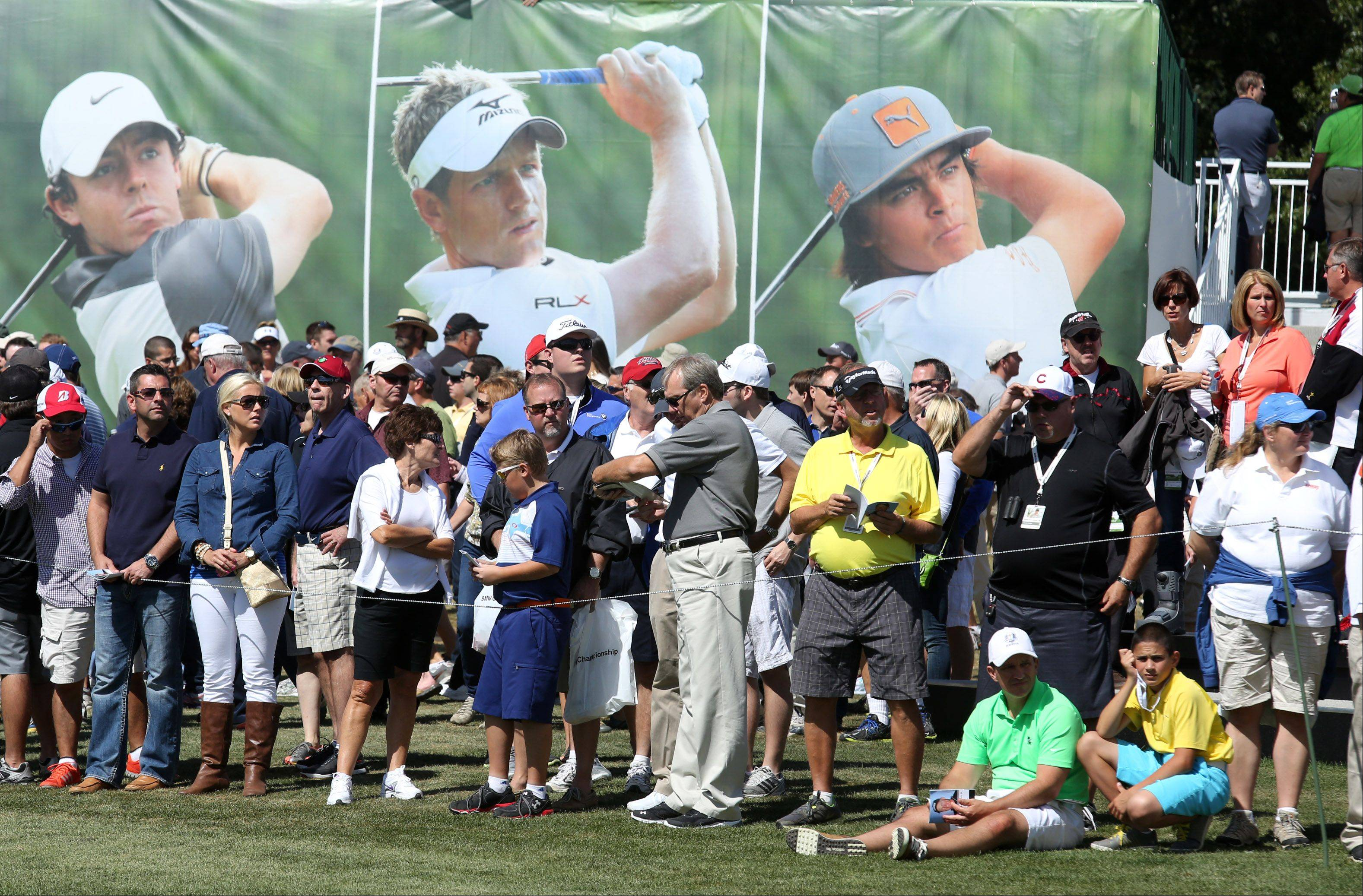Fans wait for golfers to tee off on the first hole near a leader board during the third-round of the BMW Championship at Conway Farms Golf Club in Lake Forest on Friday.