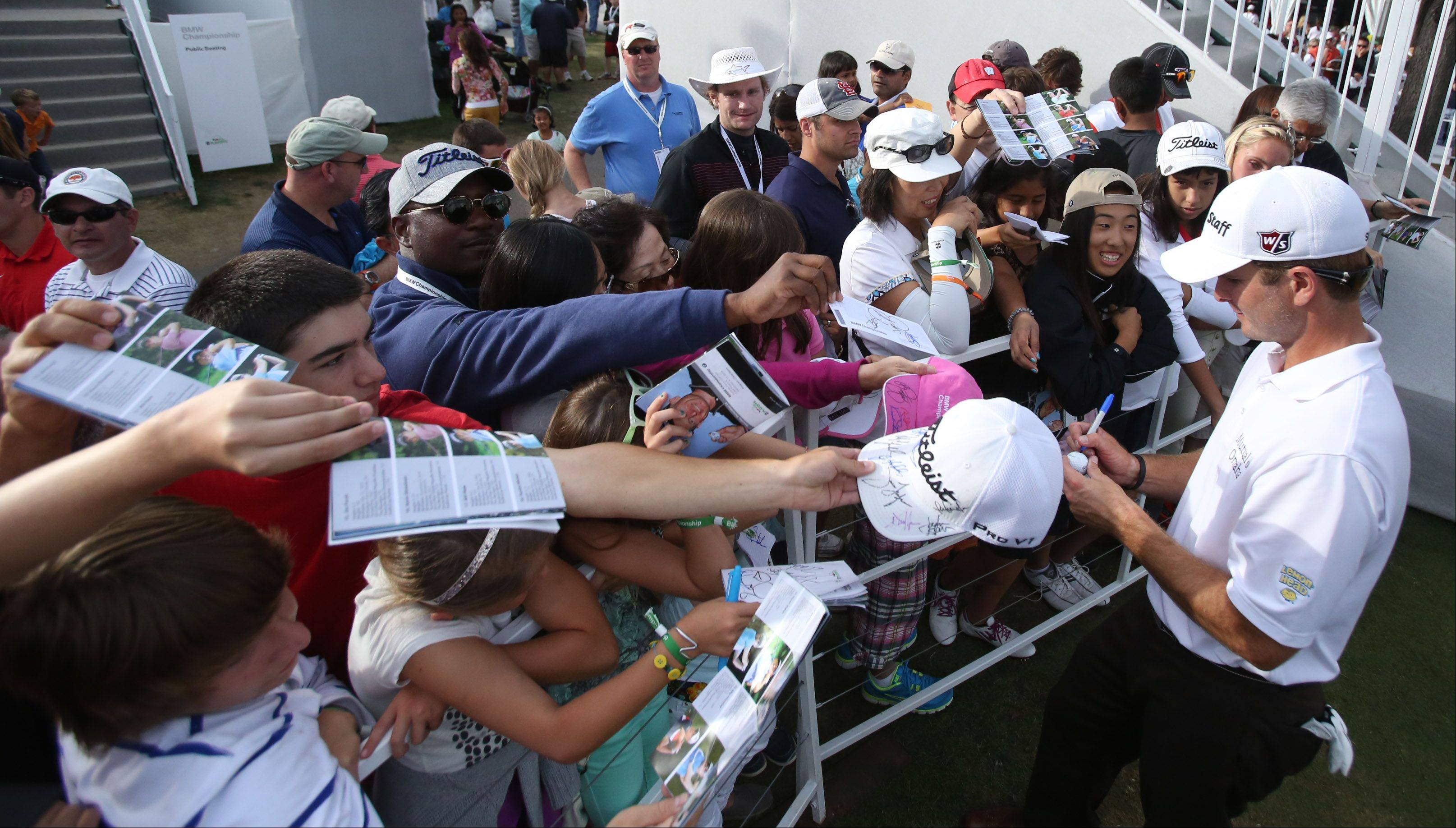 Kevin Streelman signs autographs after playing 18 holes in the third-round of the BMW Championship at Conway Farms Golf Club in Lake Forest on Friday.