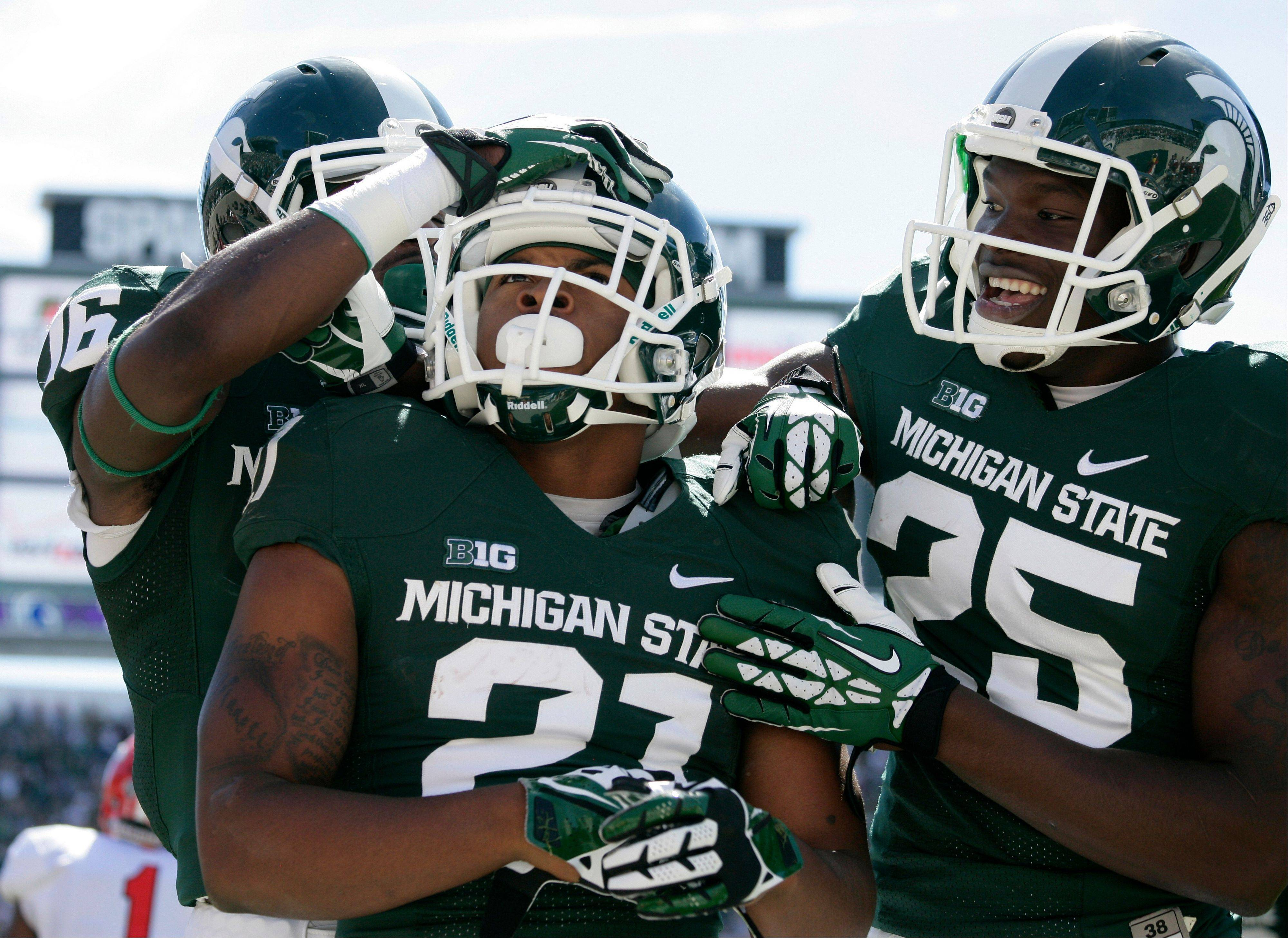 Michigan State receivers Andrew Sims Jr., center, Aaron Burbridge (16) and Keith Mumphery (25) celebrate Sims' touchdown during the first quarter of an NCAA college football game against Youngstown State, Saturday, Sept. 14, 2013, in East Lansing, Mich.