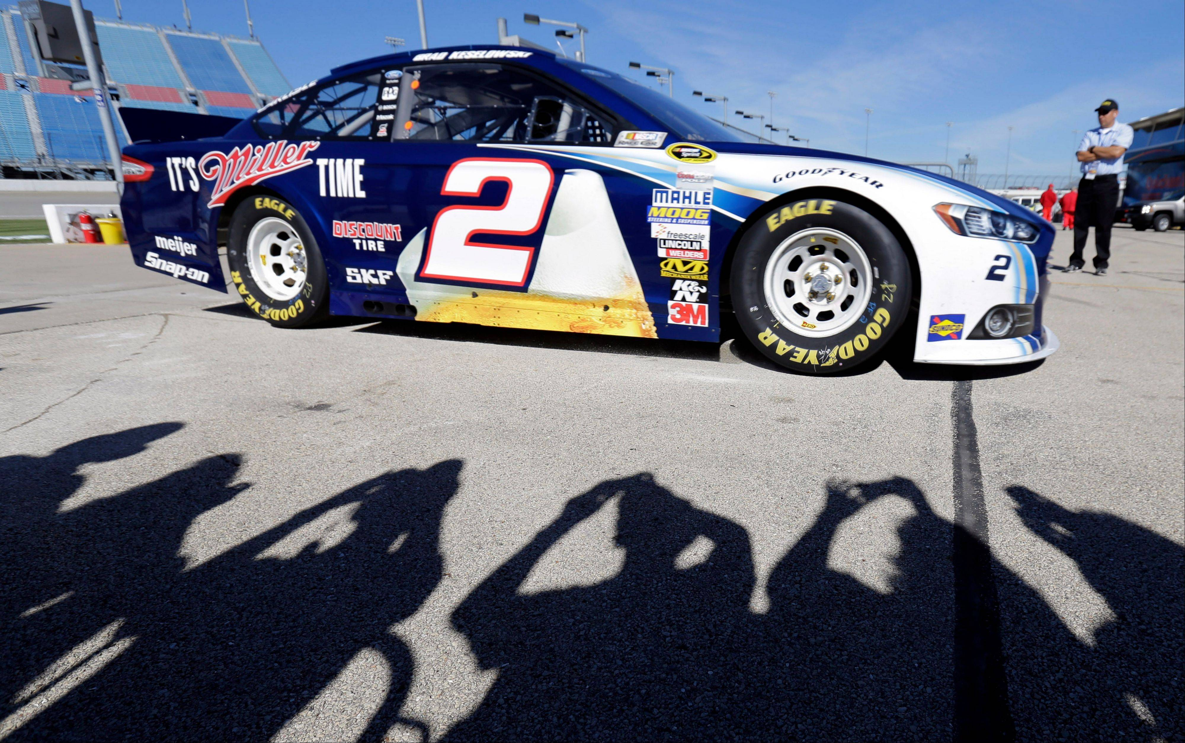 NASCAR fans take photos of Brad Keselowski's car while Brad Keselowski drives his car during practice for the NASCAR Sprint Cup Series auto race at Chicagoland Speedway in Joliet, Ill., Saturday, Sept. 14, 2013.
