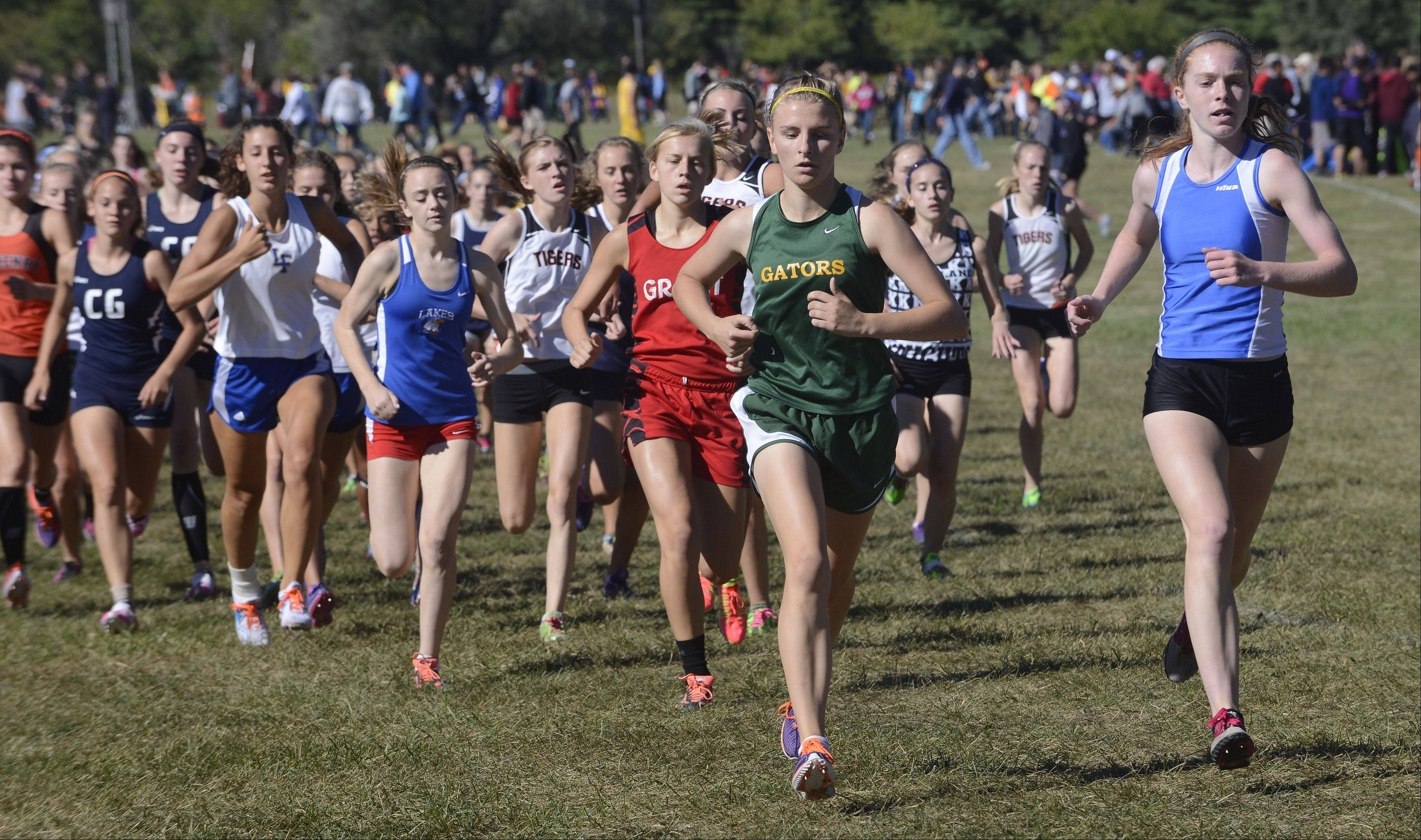 First-place finisher Meaghan Gelinas of Lake Zurich, right, makes an early move to the front during the Wauconda cross country invitational at Lakewood Forest Preserve on Saturday.