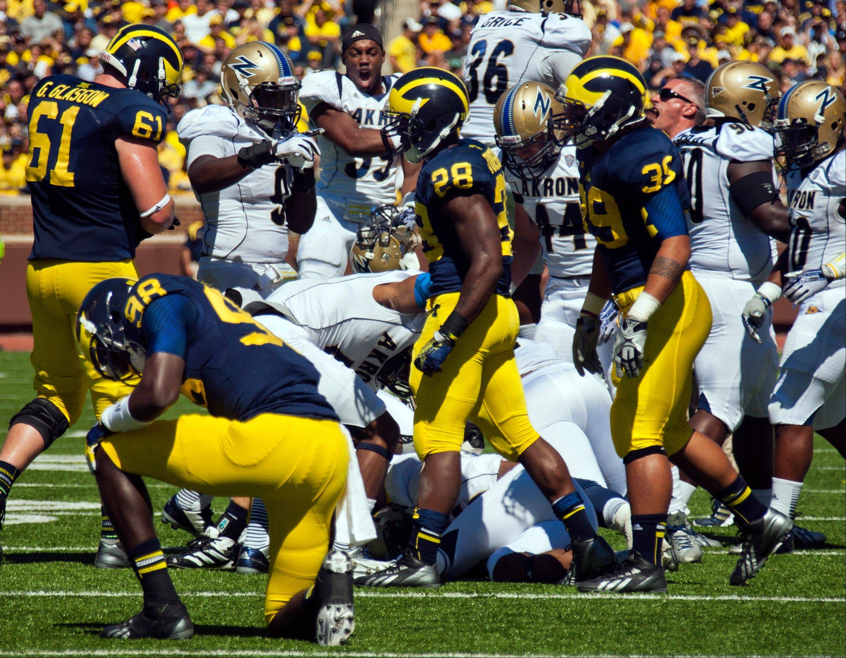 Michigan quarterback Devin Gardner (98) kneels on the field after fumbling the ball as Akron defenders celebrating the recovery in the second quarter of an NCAA college football game, Saturday, Sept. 14, 2013, in Ann Arbor, Mich.