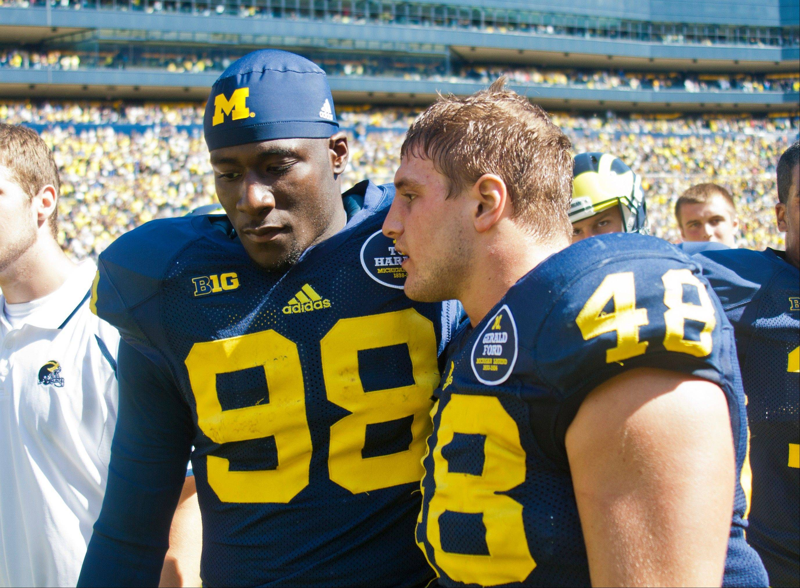 Michigan quarterback Devin Gardner (98) has words with linebacker Desmond Morgan (48) after an NCAA college football game against Akrain in Ann Arbor, Mich., Saturday, Sept. 14, 2013. Michigan won 28-24. Gardner had 3 interceptions and 1 lost fumble.