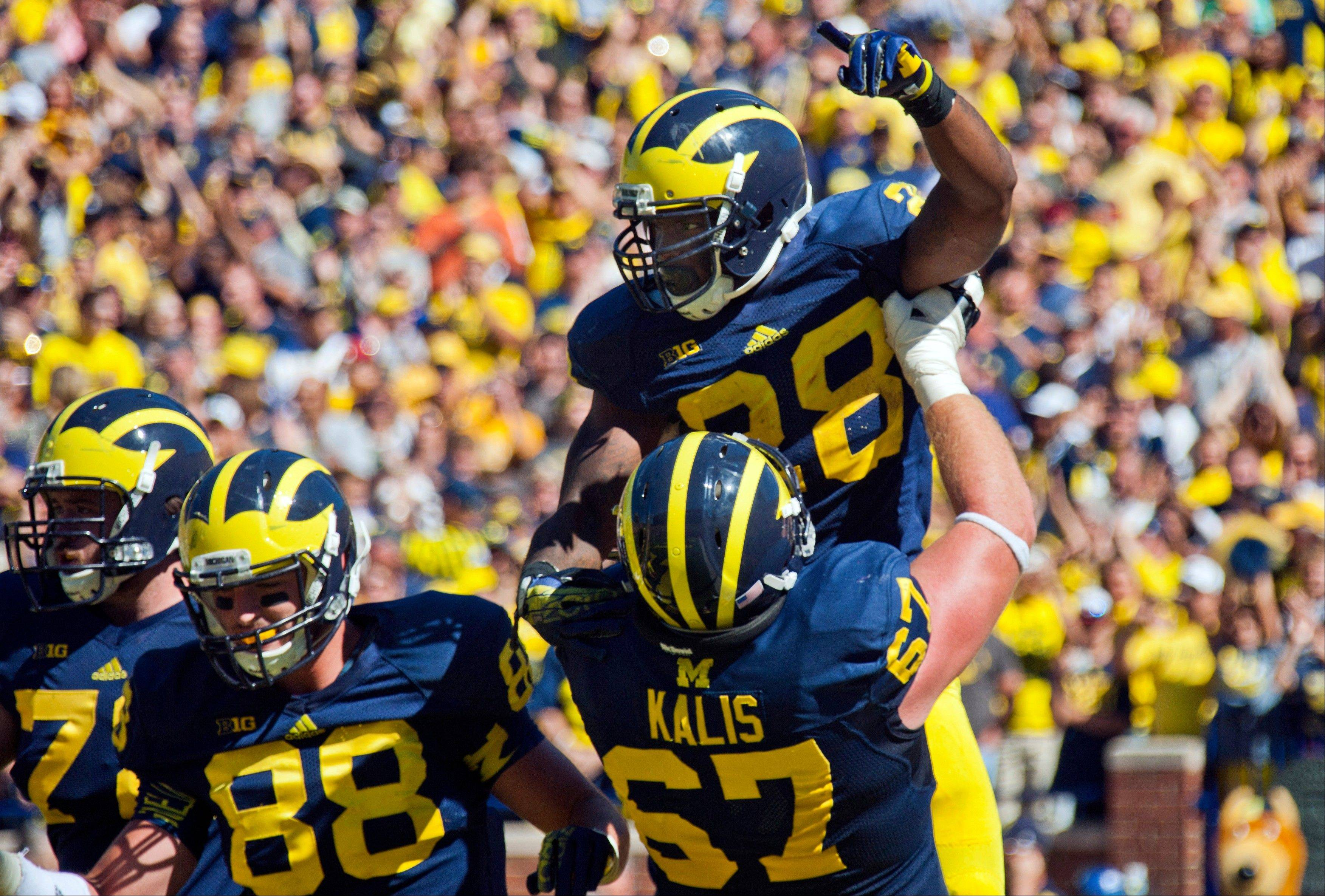 Michigan running back Fitzgerald Toussaint (28) celebrates his touchdown with offensive lineman Kyle Kalis (67) in the fourth quarter of an NCAA college football game against Akron in Ann Arbor, Mich., Saturday, Sept. 14, 2013. Michigan won 28-24.