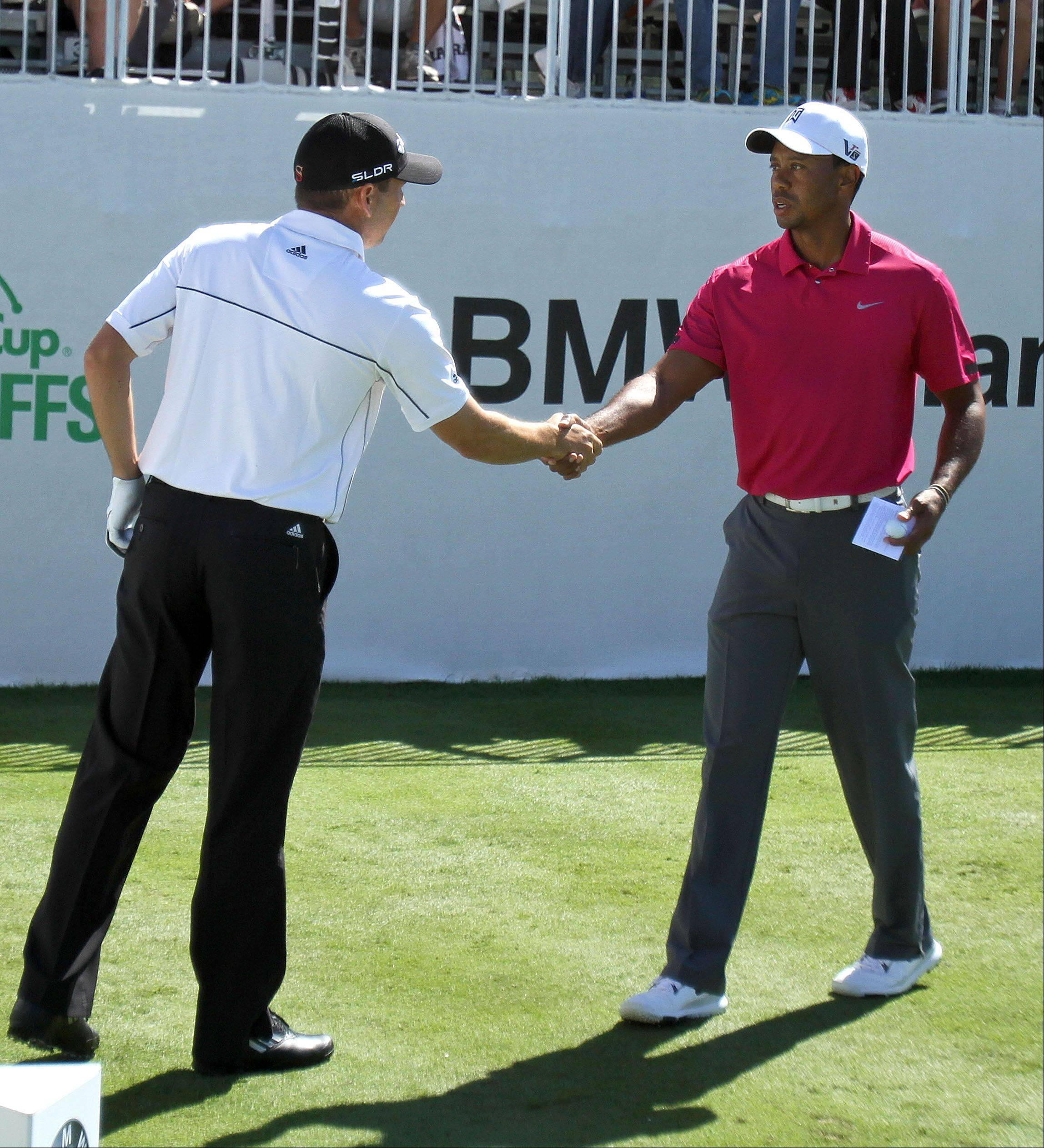 Sergio Garcia and Tiger Woods shake hands on the first tee during the third-round of the BMW Championship at Conway Farms Golf Club in Lake Forest Saturday. The two were all business and left whatever bad blood that remains between the two behind them.
