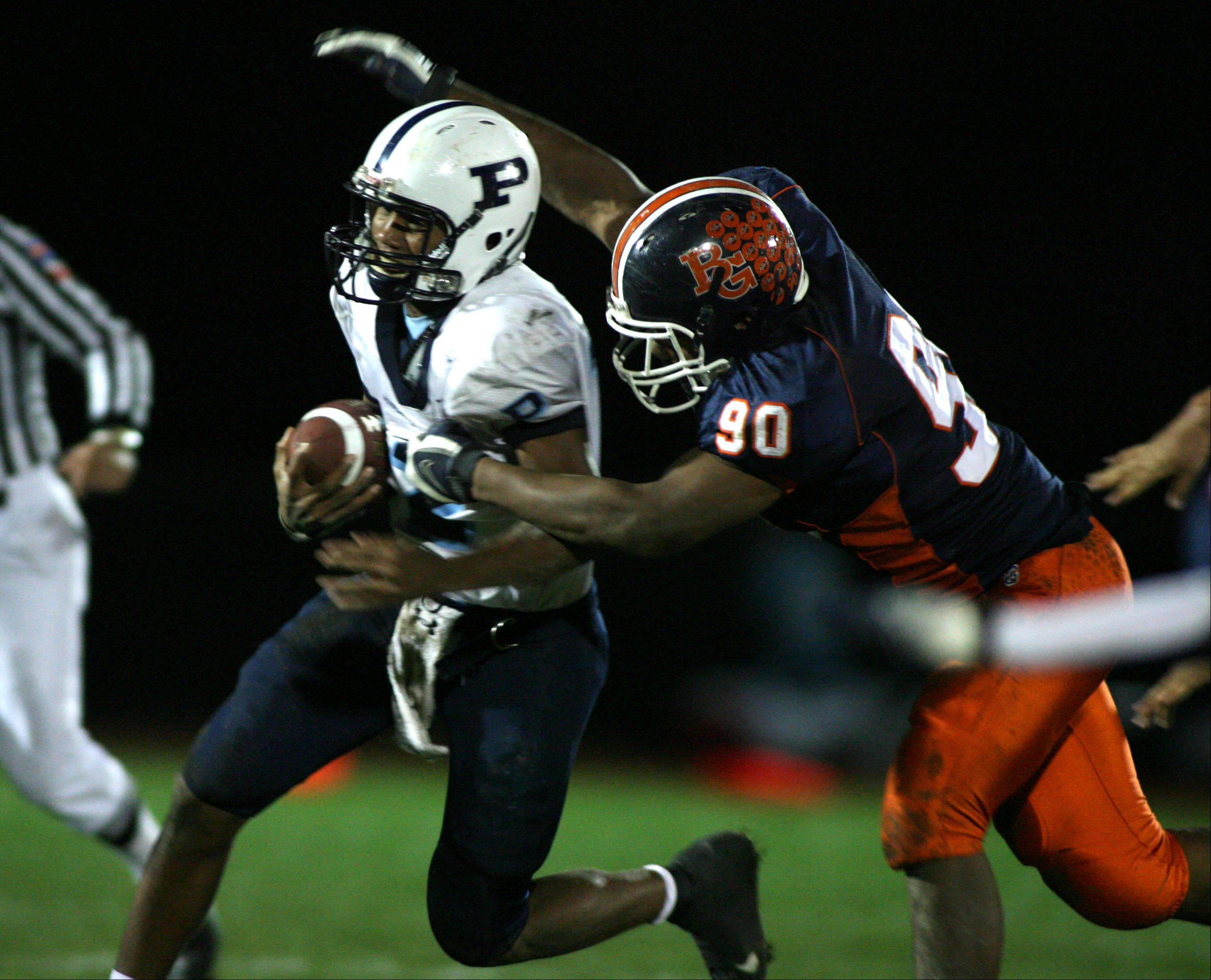 Former Buffalo Grove defensive star Alan Baxter, right, brings down former Prospect quarterback Miles Osei. Both players were recruited by NIU, but Baxter stayed and became a standout defensive end while Osei chose to attend Illinois, where he plays wide receiver.