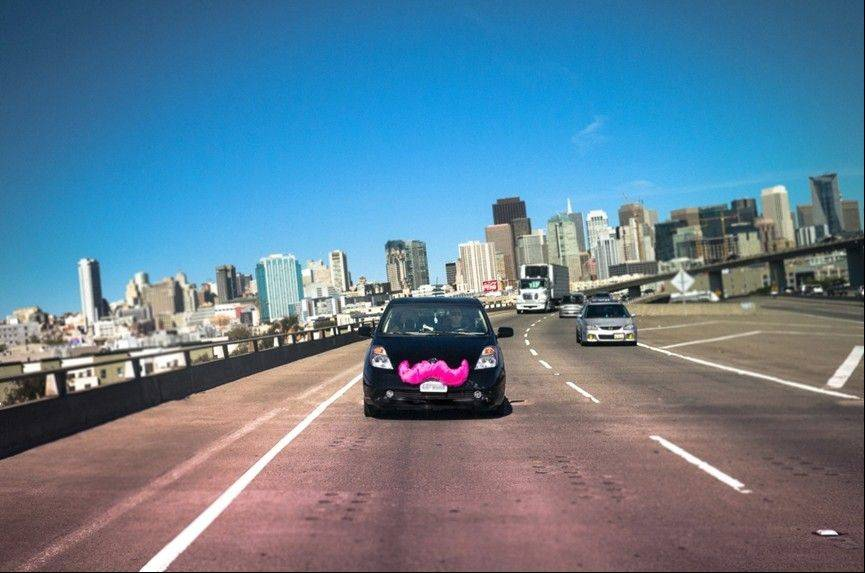 A Lyft car on the road with a signature pink mustache. Lyft is a San Francisco-based mobile app that lets users request rides from drivers willing to chauffeur them for a fee.