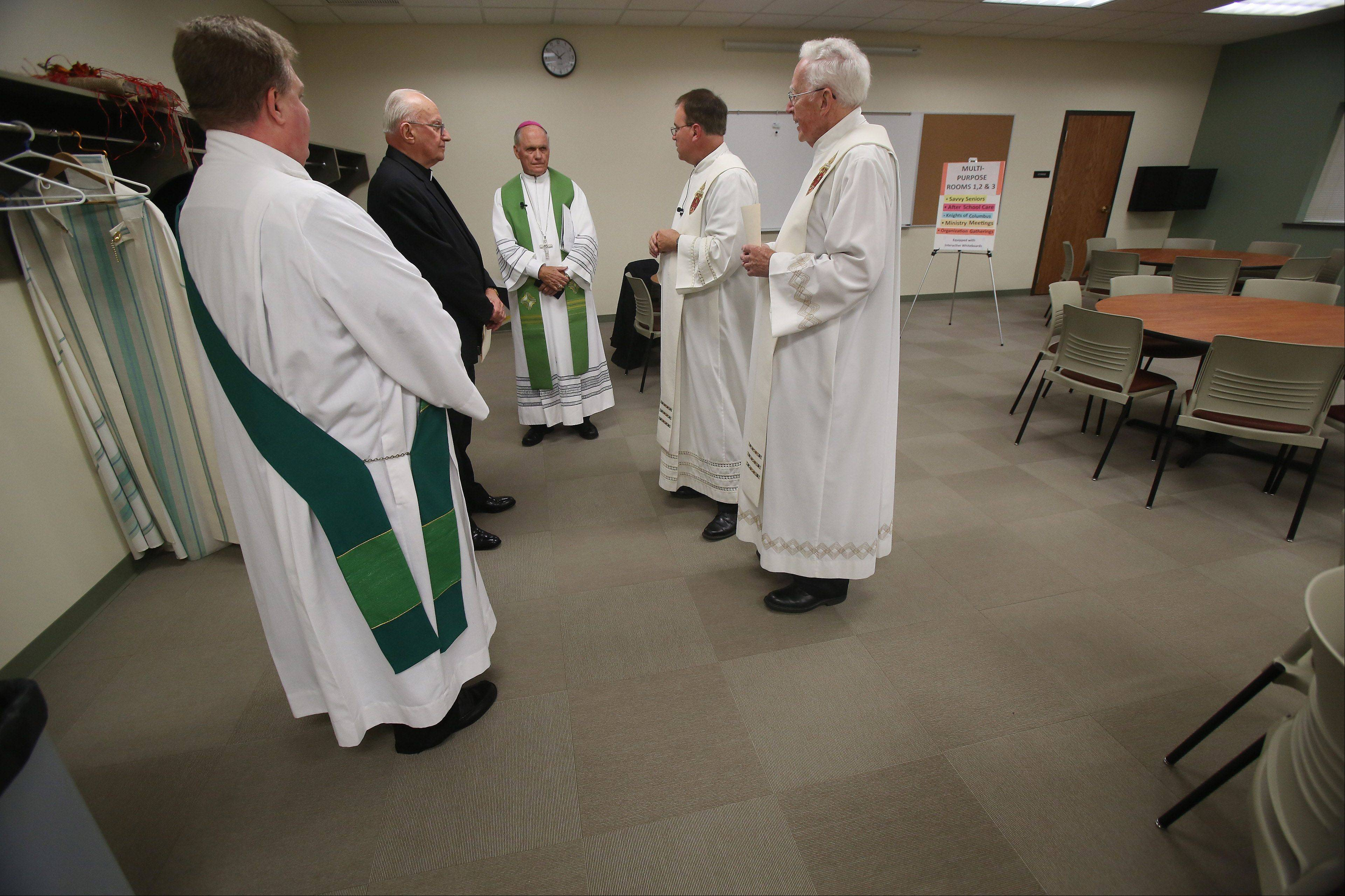 Priests and bishops, including Bishop George Rassas, center, gather in one of the new multipurpose rooms before the dedication ceremony Sunday at Prince of Peace Catholic Church in Lake Villa. The church built a new, $5.3 million, 42,00-square-foot Parish Life Center, that includes a new gym, classrooms, a library, fine arts room, computer classrooms and meeting rooms.