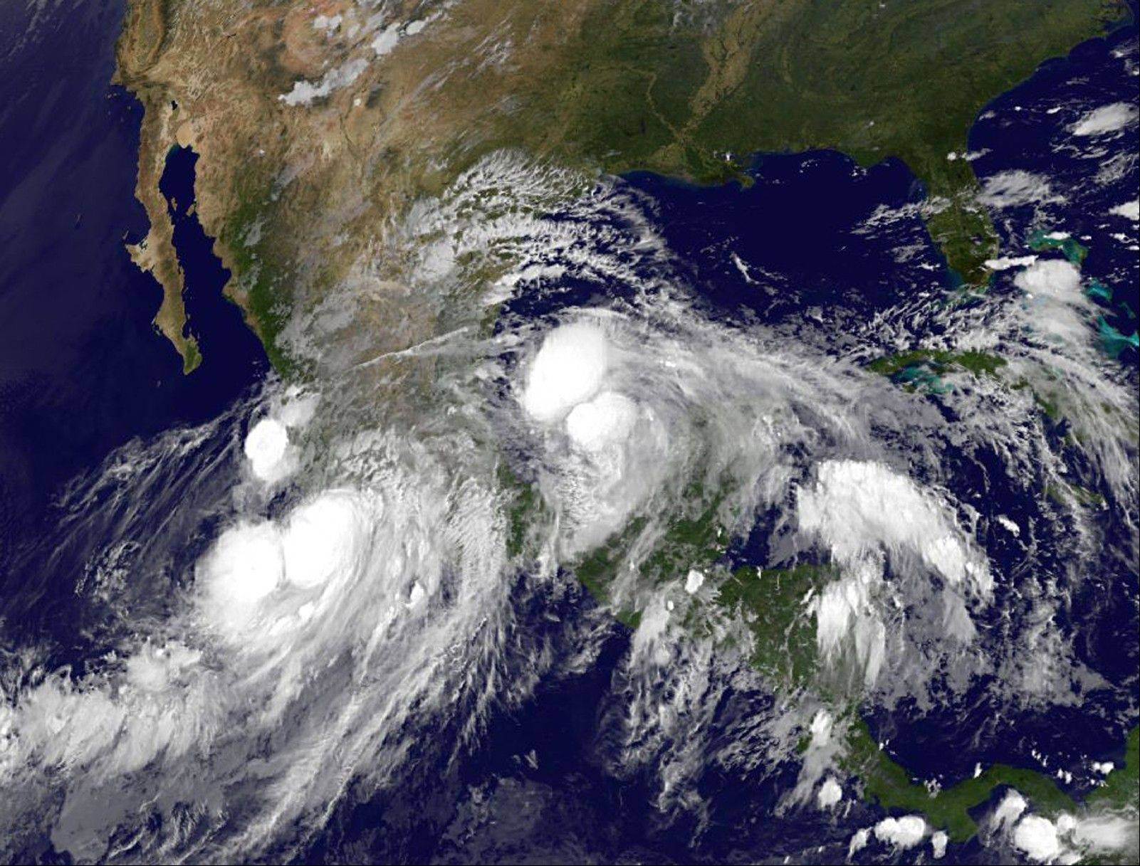 In this image provided by NOAA taken Sunday shows hurricane Ingrid in the Gulf of Mexico approaching the coast of Mexico and tropical storm Manuel just off the western coast of Mexico.