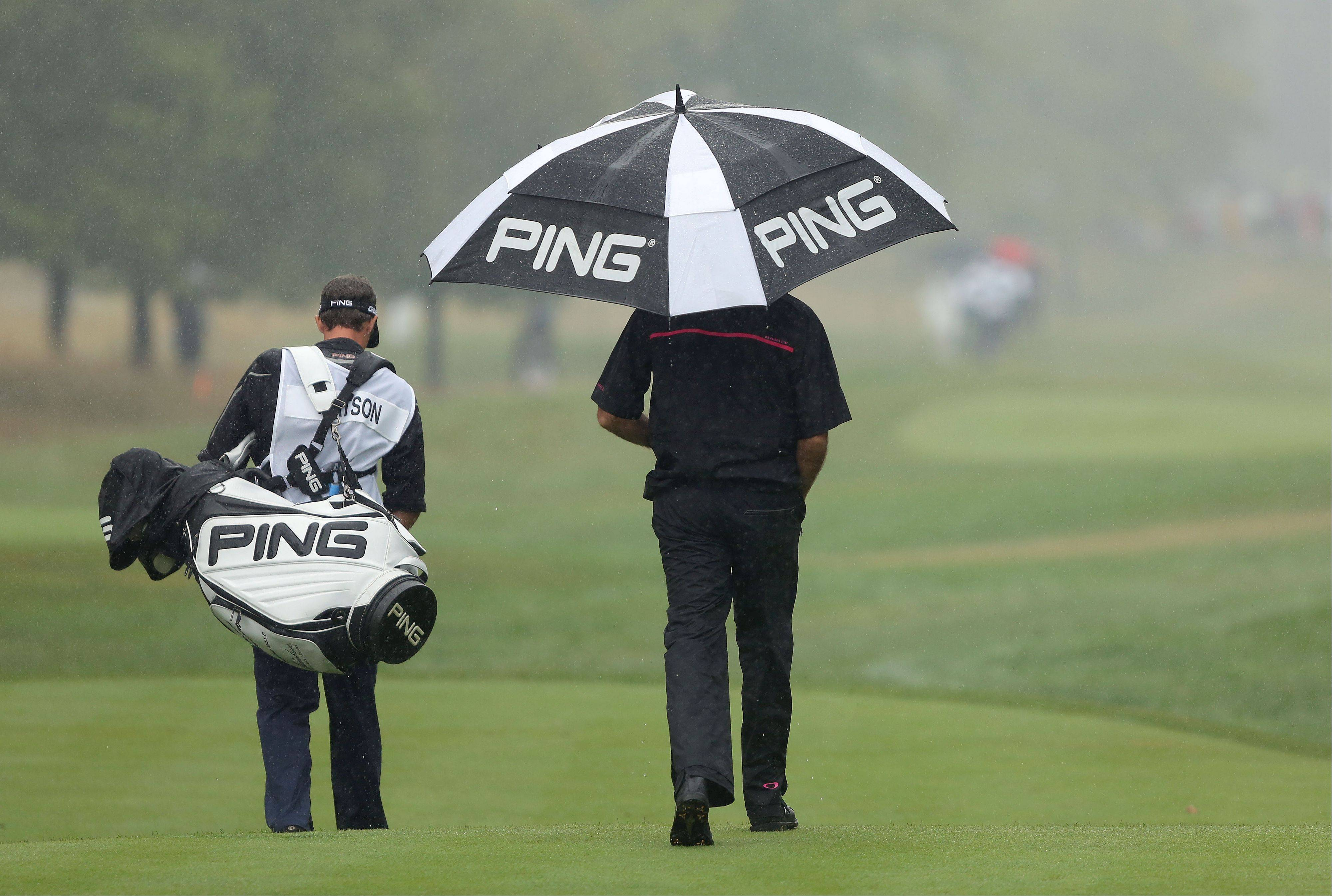 Bubba Watson and his caddie head down the third hole as they attempt to play after the first rain delay during the final round of the BMW Championship at Conway Farms Golf Club in Lake Forest Sunday.