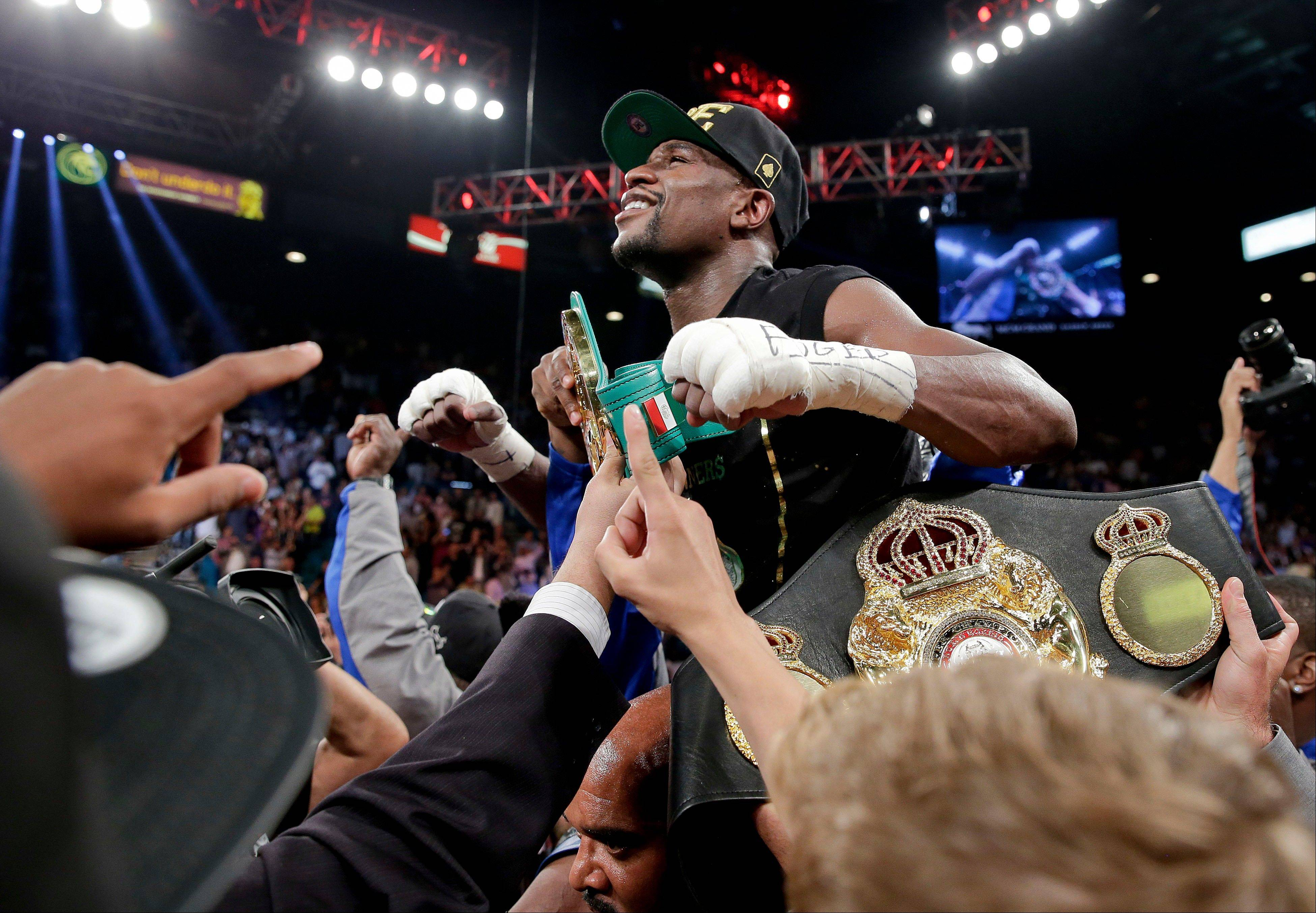 Floyd Mayweather Jr. celebrates after defeating Canelo Alvarez in a 152-pound title fight, Saturday, Sept. 14, 2013, in Las Vegas. (AP Photo/Eric Jamison)