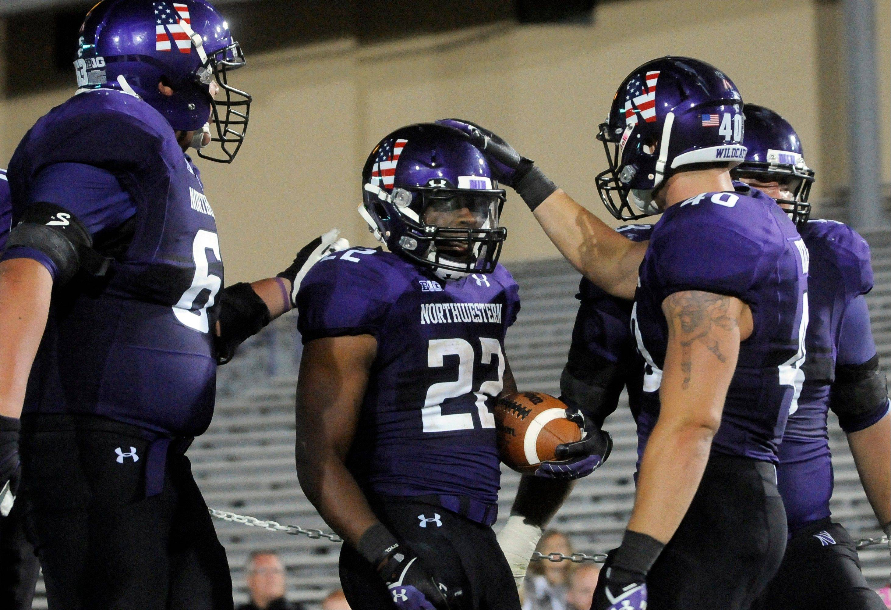Northwestern's Treyvon Green (22) celebrates his touchdown against Western Michigan with teammates Ian Park (63) Dan Vitale (40) and Geoff Mogus (53)during the fourth quarter of an NCAA college football game in Evanston, Ill., Saturday, Sept. 14, 2013. (AP Photo/Matt Marton)