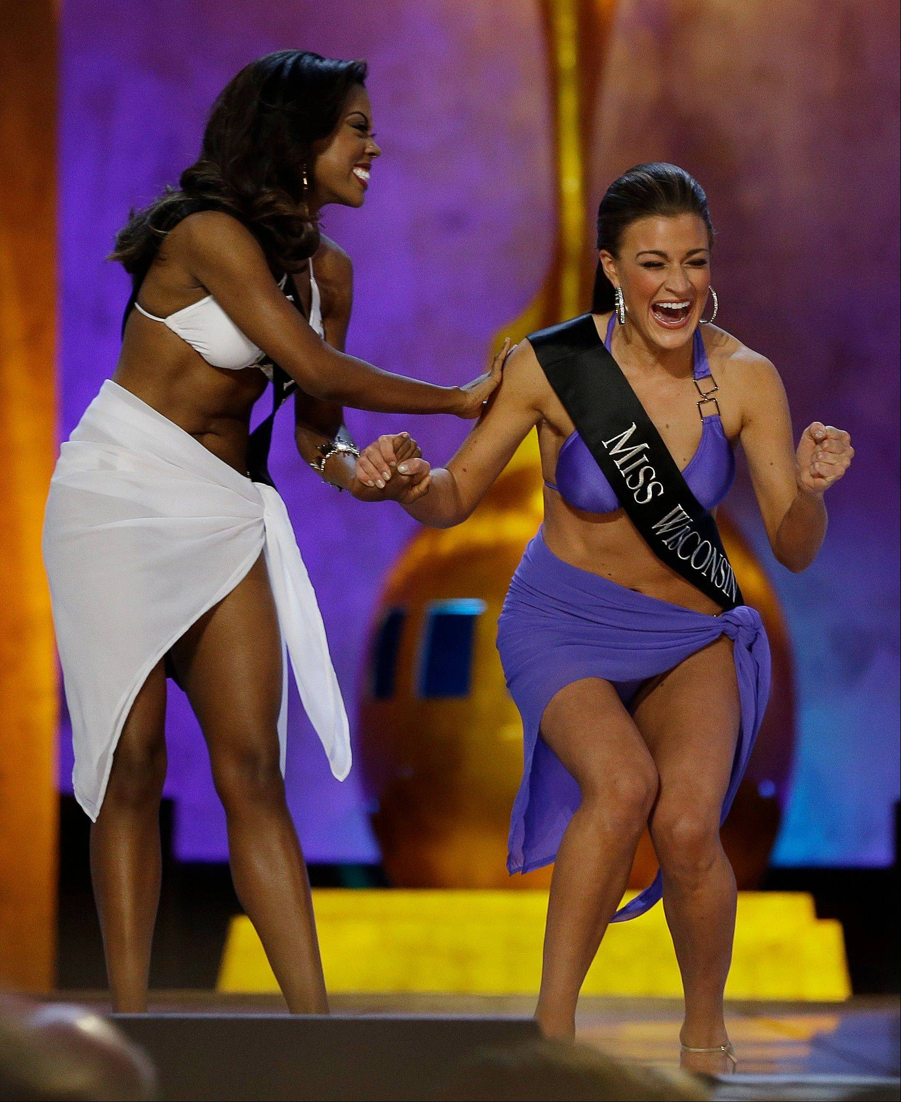 Miss Wisconsin Paula Mae Kuiper, right, reacts after finding out she's advancing beyond the lifestyle round as Miss Texas Ivana Hall congratulates her during the Miss America 2014 pageant, Sunday, Sept. 15, 2013, in Atlantic City, N.J.