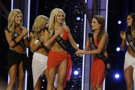 Miss Kansas Theresa Vail, left, reacts after advancing beyond the lifestyle competition as Miss Kentucky Jenna Day, right, holds her hand during the Miss�America 2014 pageant, Sunday, Sept. 15, 2013, in Atlantic City, N.J.