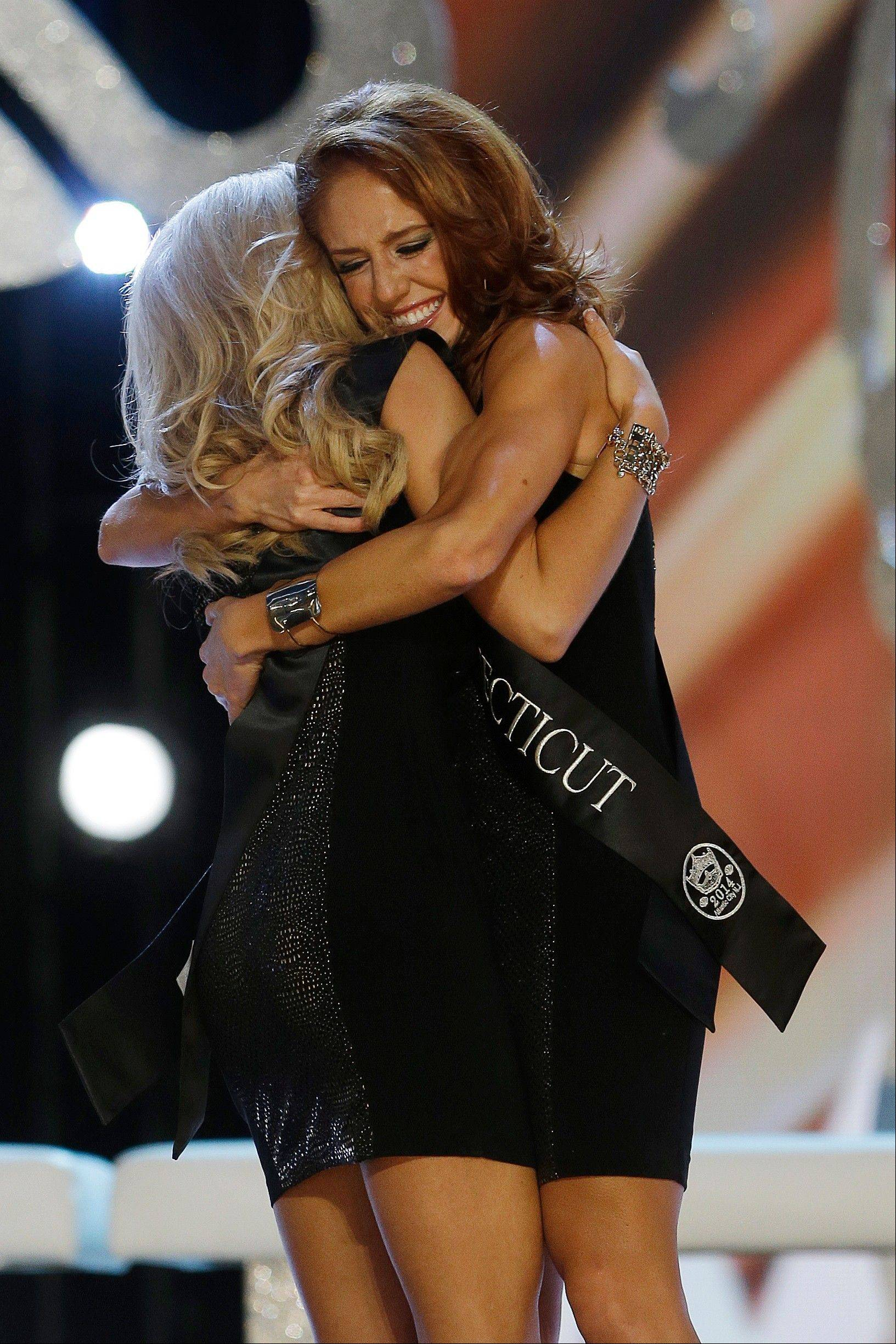 Miss Connecticut Kaitlyn Tarpey, right, hugs Miss Georgia Carly Mathis during the Miss America 2014 pageant, Sunday, Sept. 15, 2013, in Atlantic City, N.J.