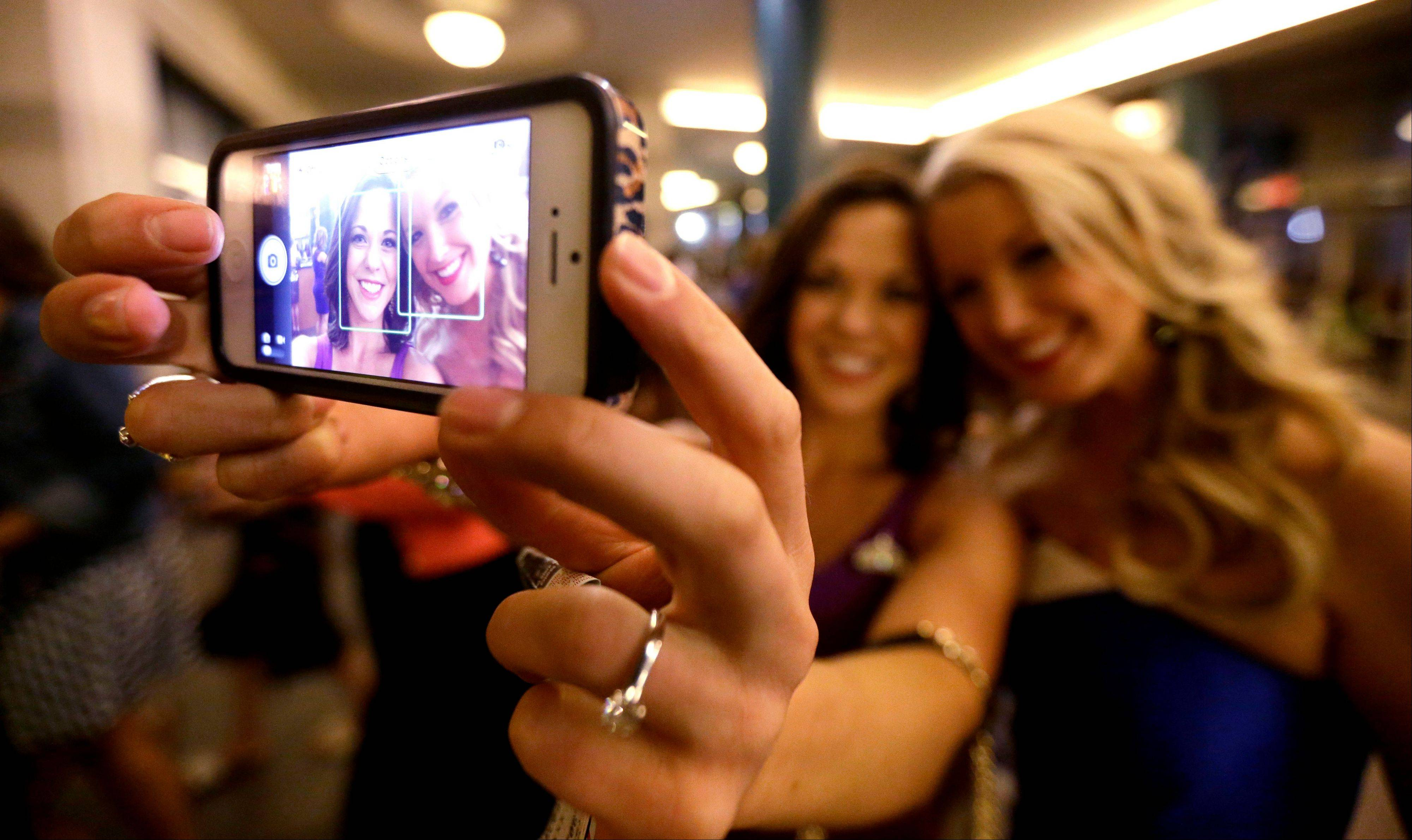 Miss America pageant alumni Miss South Dakota Calista Kirby, left, and Miss Rhode Island Kelsey Fournier take a photograph of themselves with a phone before the Miss America 2014 pageant, Sunday, Sept. 15, 2013, in Atlantic City, N.J. The former misses participated in last year's contest in Las Vegas.