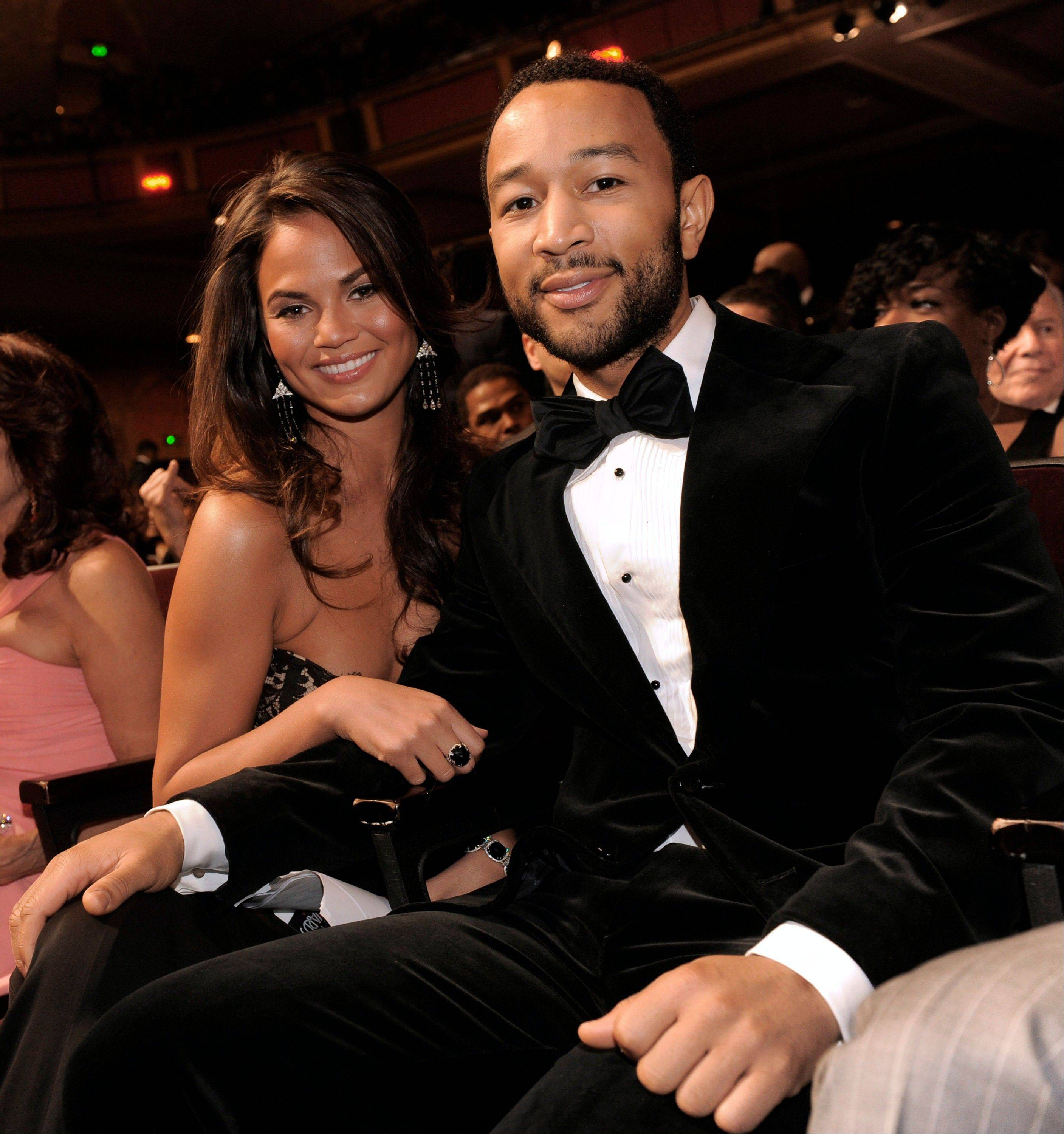 This Feb. 26, 2010 file photo shows John Legend, right, and Christine Teigen at the 41st NAACP Image Awards in Los Angeles. Legend is officially off the market. The R&B crooner's representative said Legend married Teigen on Saturday at the Villa Pizzo in Lake Como, Italy. Legend, 34, and Teigen, 27, got engaged in 2011.