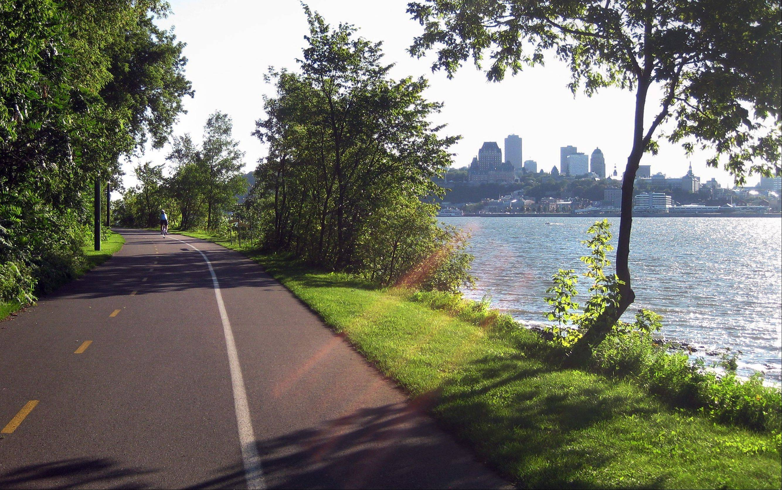 A cyclist rides along the St. Lawrence River across from Quebec City on an off-road trail in Levis.