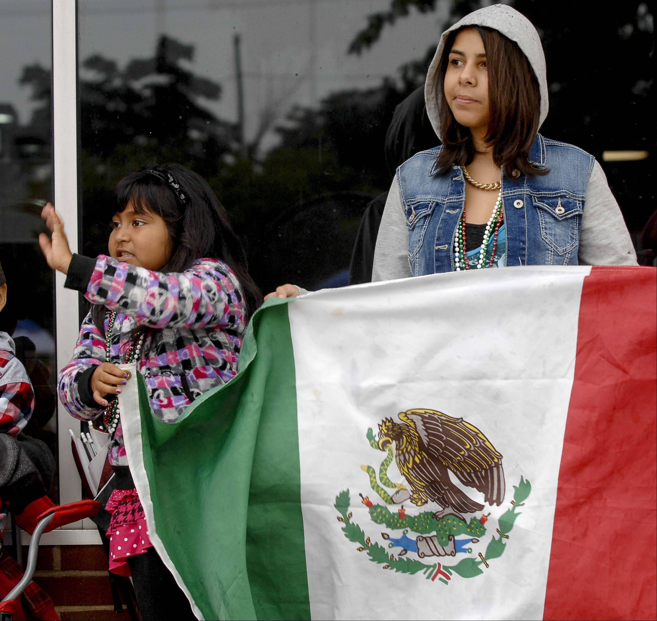 Cindy Garcia, 7, and Crystal Lopez, 15, of Aurora, hold up a Mexican Flag as they watch the Fiestas Patrias parade in downtown Aurora, Sunday.