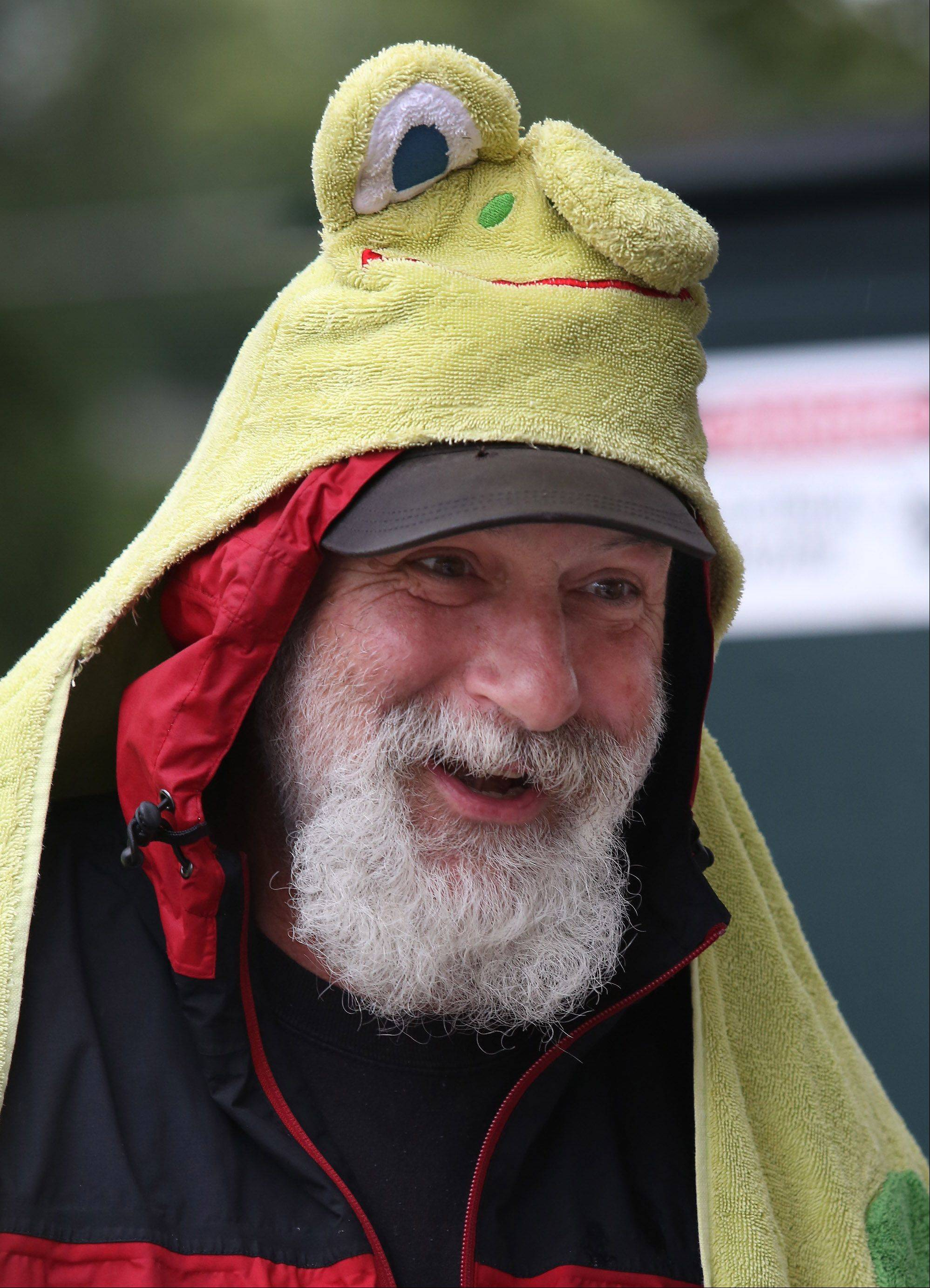 Des Plaines Park District supervisor Ed Kelley wears a frog towel over his head to protect him from the rain during the Des Plaines Fall Fest Sunday at Lake Park. Constant rainfall resulted in sparse crowds to the event.