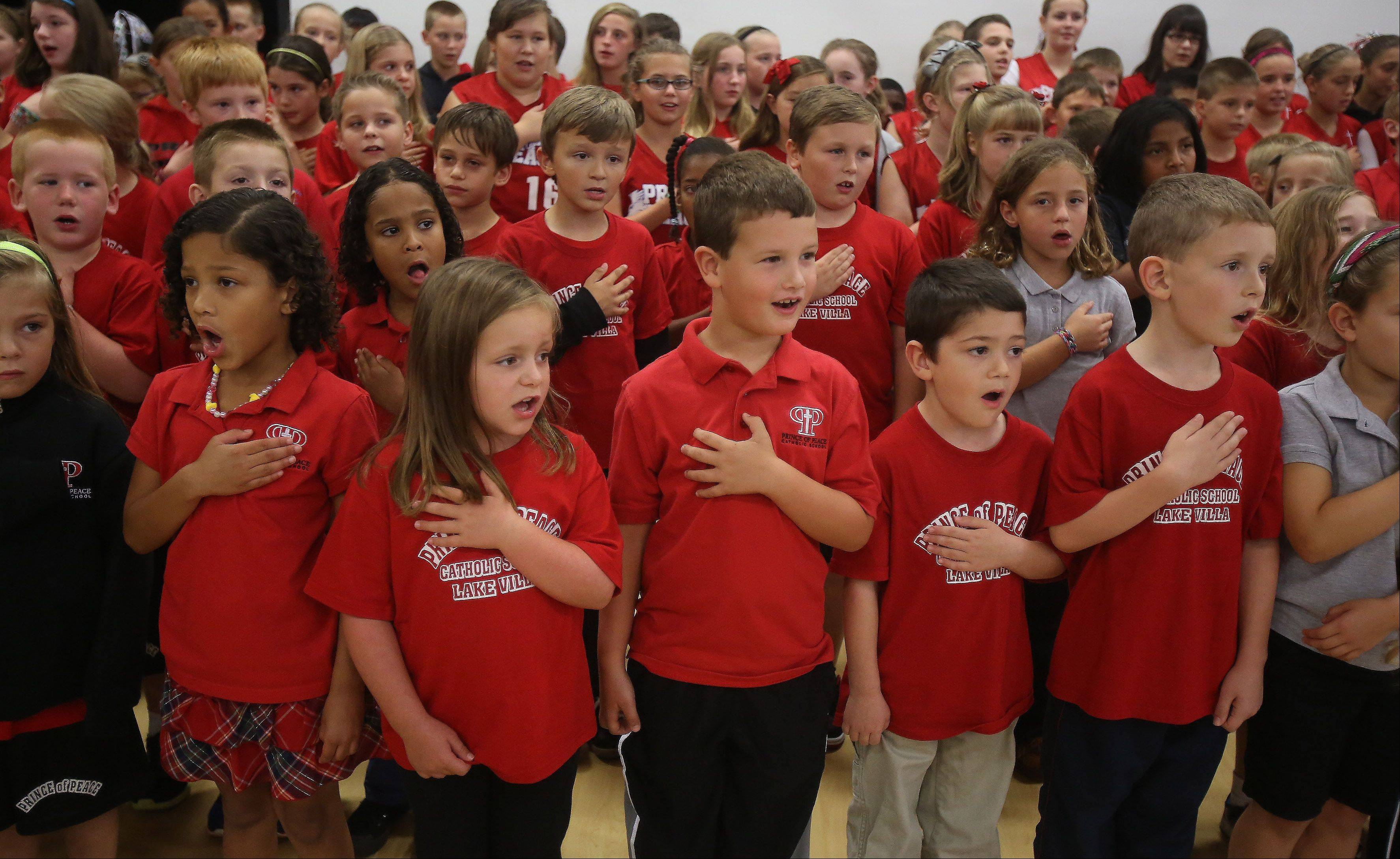 Young Redhawk students sing the national anthem during the dedication ceremony Sunday at Prince of Peace Catholic Church in Lake Villa. The church built a new 42,00-square-foot Parish Life Center, that included a new gym, preschool and kindergarten classes, a library, fine arts room, computer classrooms, and meeting rooms.