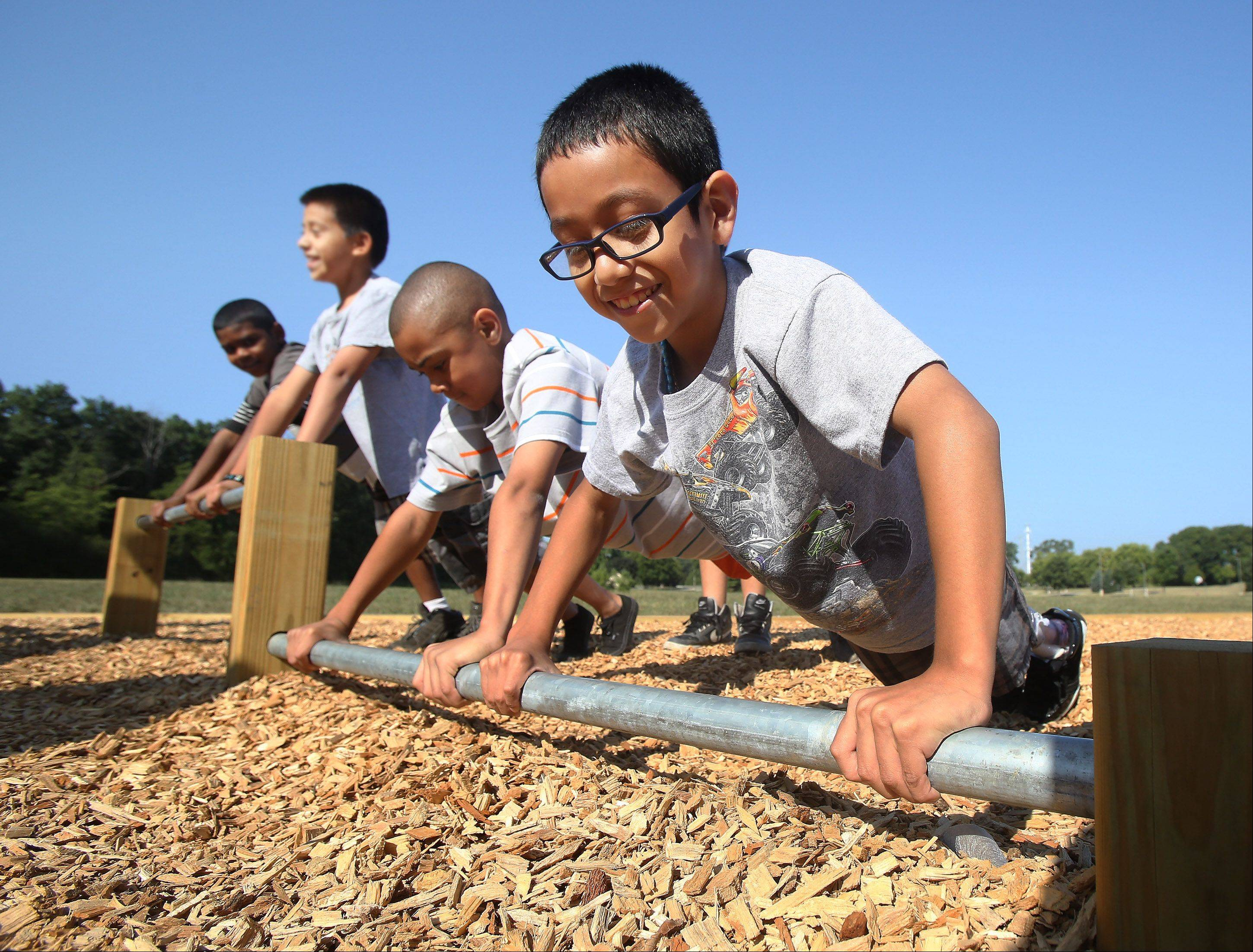 Fifth graders Angel Cruz, right, Isaiah Nixon and other students, do pushups on the new Fit-Trail station Tuesday at Woodland Intermediate School in Gurnee. The new fitness station will be used for students during the school day and available to the community after school hours.
