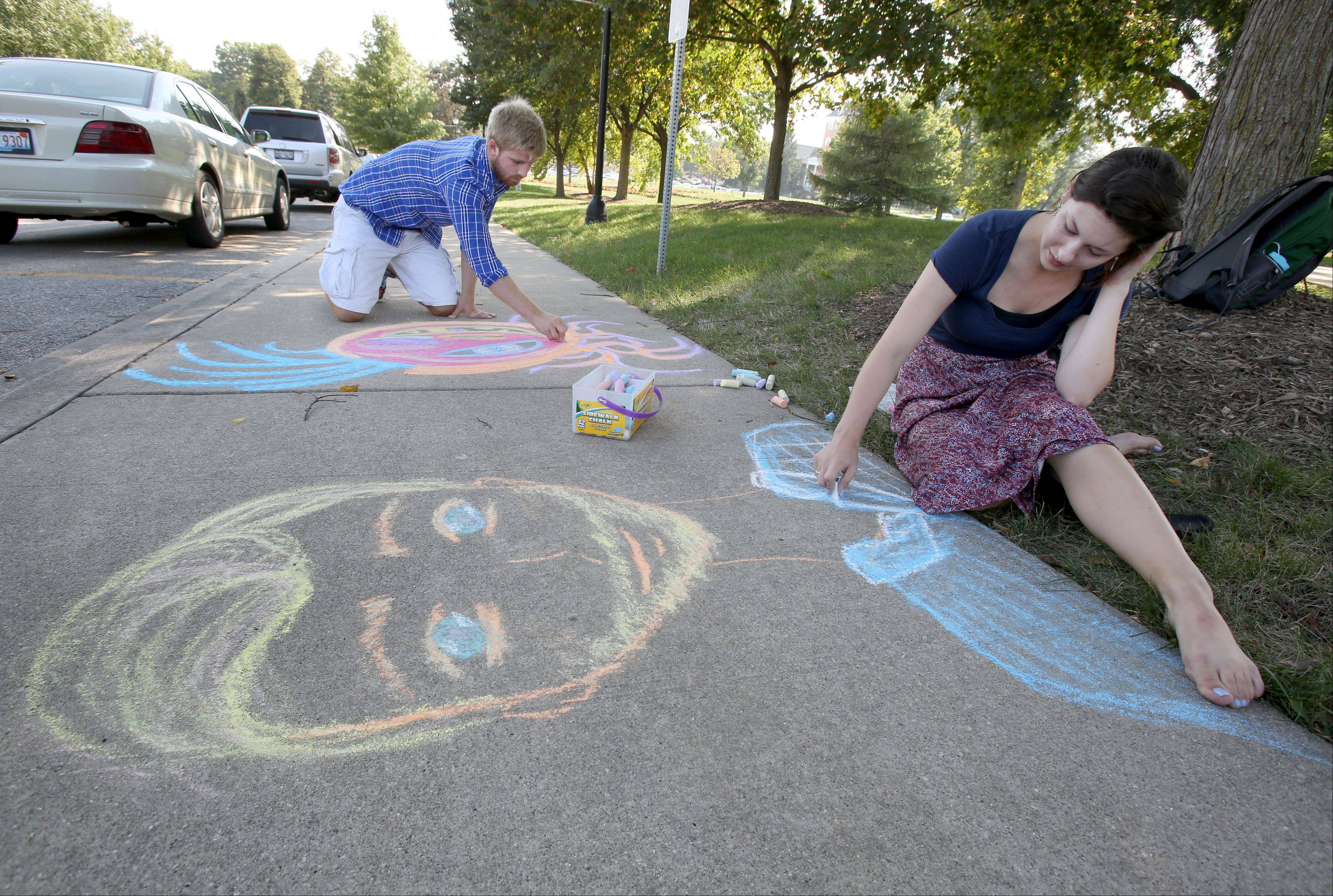 "Beau Westlund, left, helps Christabel Barry, both seniors at Wheaton College, work on chalk drawings on the campus on Tuesday. Barry will be making the chalk drawings around campus for the next 20 days as a stunt called Playing with Chalk, which is part of a writing class project. ""This is my way of making time for art and creativity and inviting other people to help"". she said."