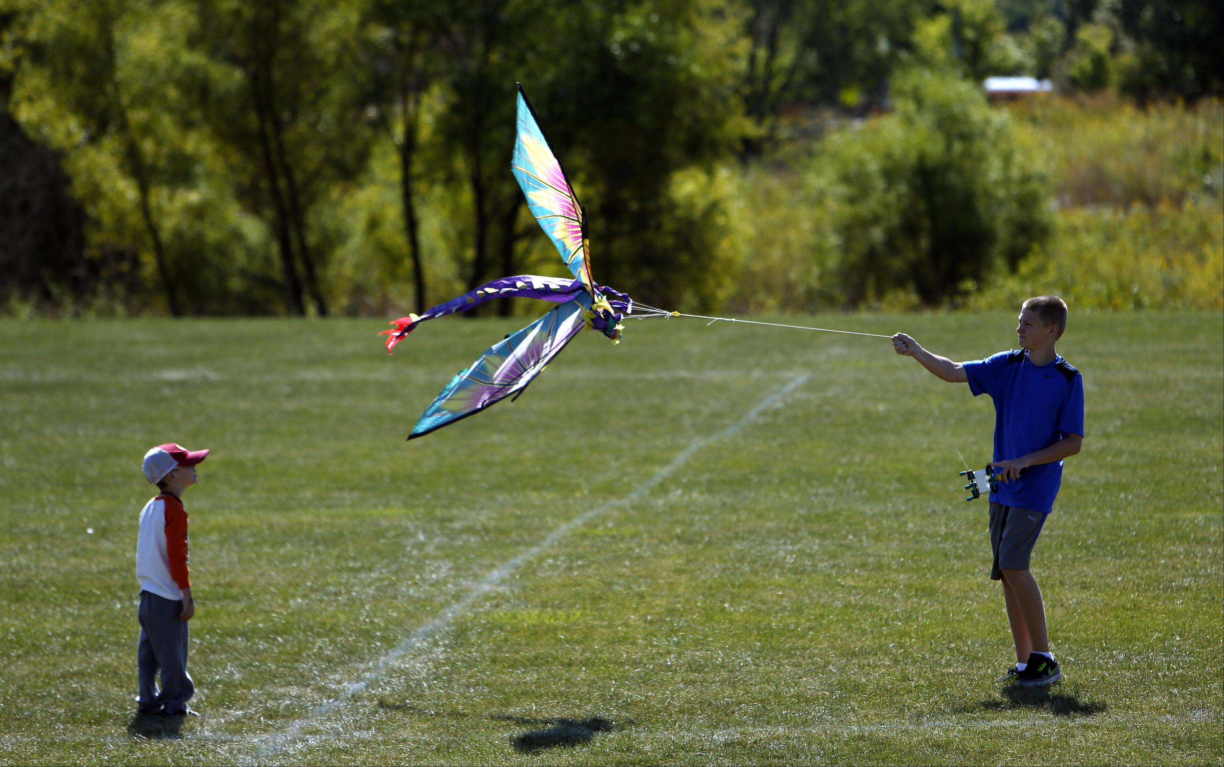With his younger brother Mason Wynn, 4, looking on and offering support thirteen-year-old Brandon Jenkins, both of Geneva, try to get their dragonfly kite airborne during the third annual Geneva Park District Kite Festival at Peck Farm Park in Geneva Saturday.