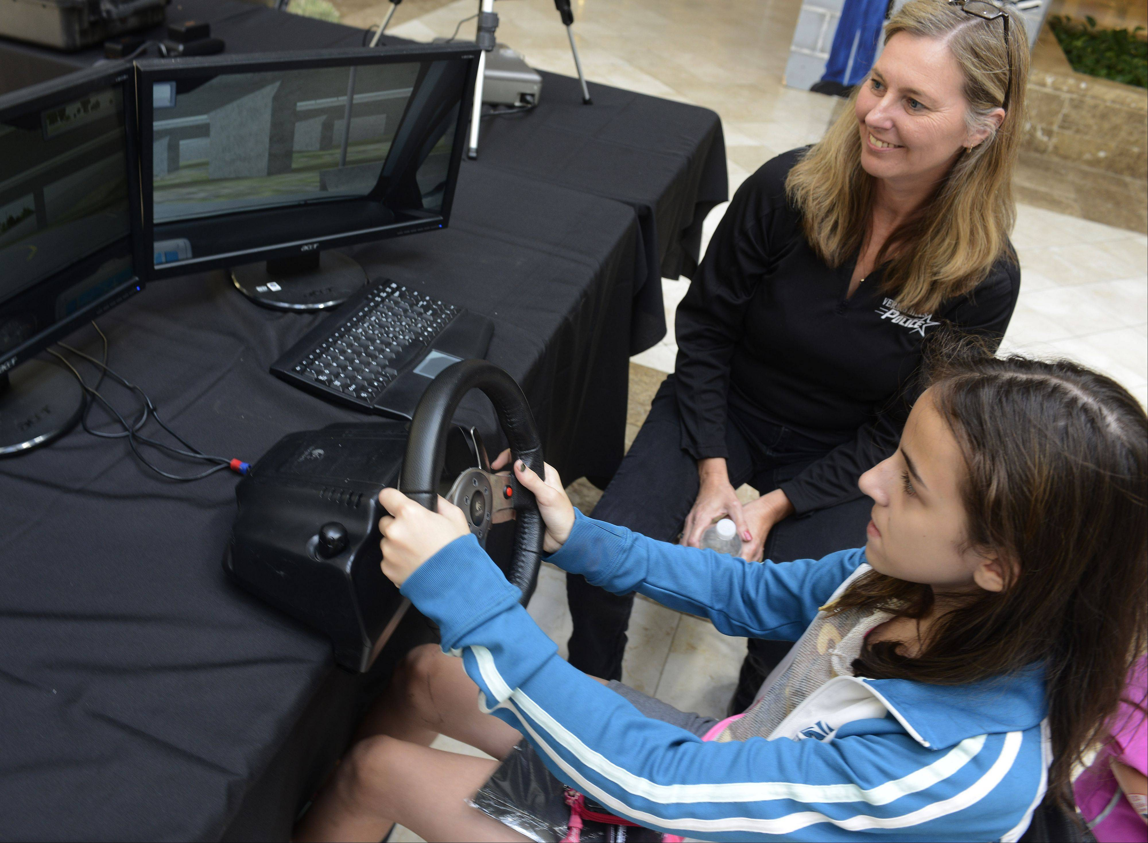 Aleasha Klegerman, 13, of Vernon Hills, tries out a driving simulator with the help of Vernon Hills Police Department Administrative Assistant Liz Koehl during the 9th annual Law Enforcement Exhibition at the Westfield Hawthorn Mall in Vernon Hills Saturday.