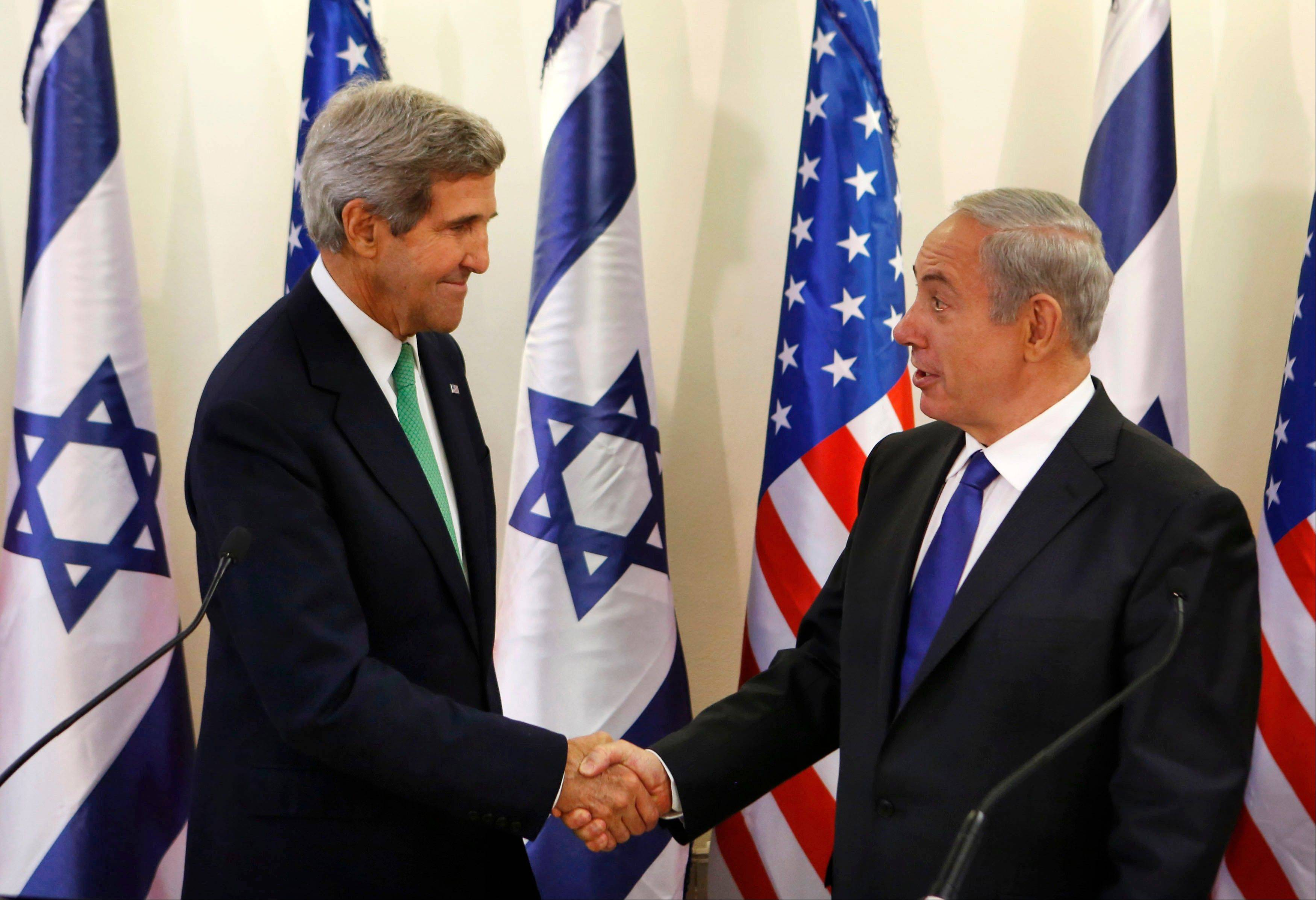 "Secretary of State John Kerry, left, shakes hands with Israel's Prime Minister Benjamin Netanyahu at the prime minister's office in Jerusalem Sunday. Kerry on Sunday sent a strong warning to Syria, saying ""the threat of force is real"" if it does not carry out an internationally brokered agree"