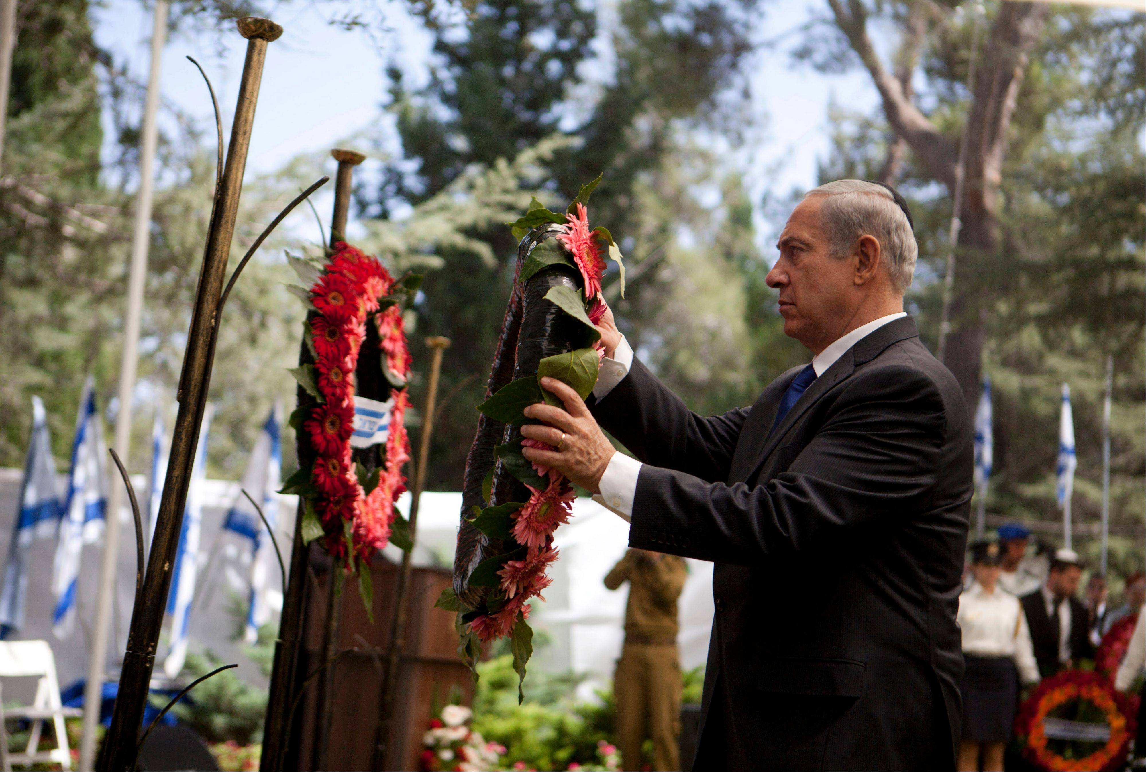 Israeli Prime Minister Benjamin Netanyahu hangs a wreath on a pole during the state memorial ceremony for soldiers, fallen during the 1973 Arab-Israel War, which Israelis call the Yom Kippur War, in Jerusalem, Sunday, Sept. 15, 2013. Israeli leaders expressed cautious hope Sunday about a U.S.-Russia agreement that would require Syria to identify and eliminate its chemical weapons by mid-2014, as U.S. Secretary of State John Kerry arrived in the region to discuss the deal.