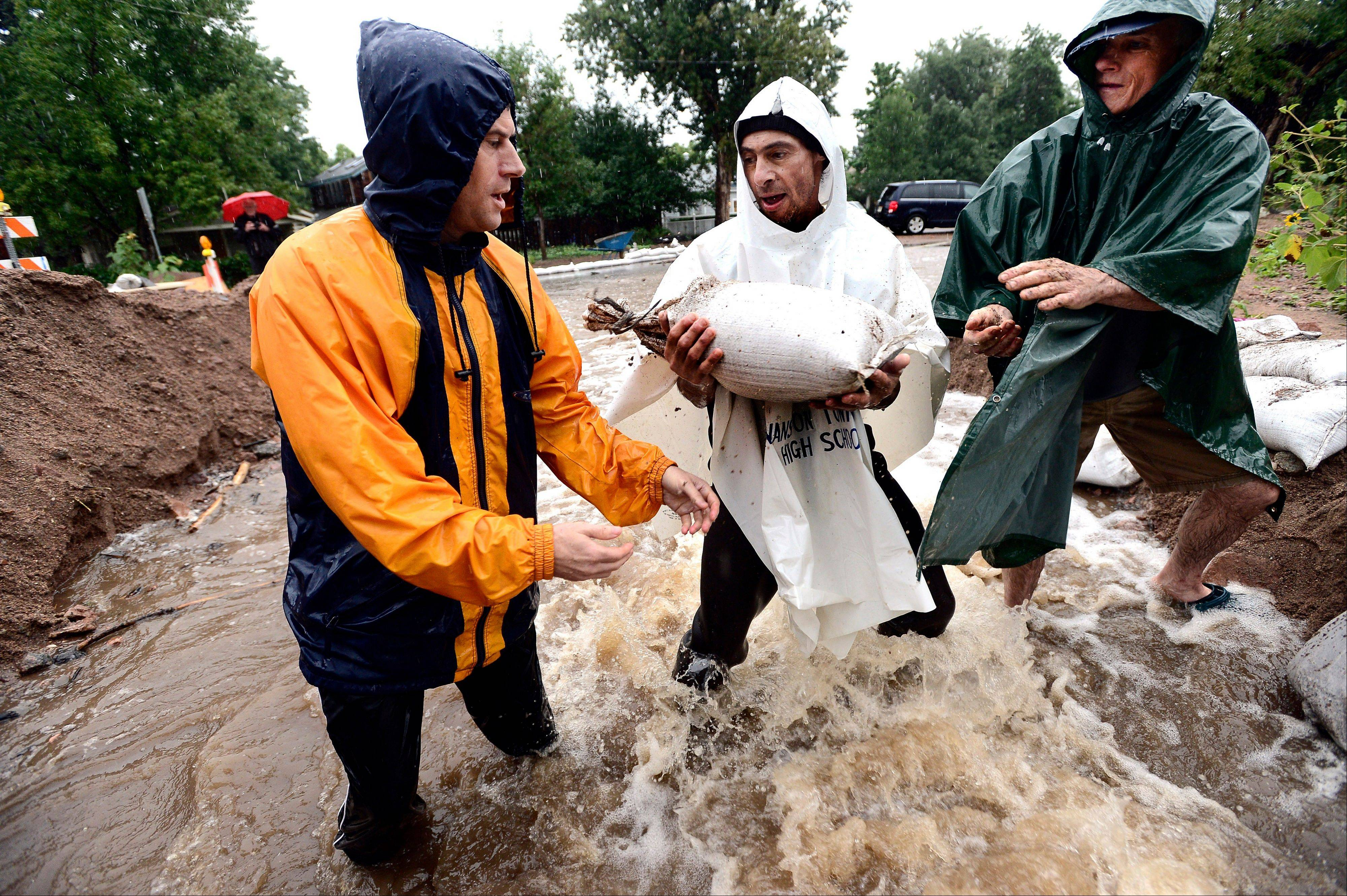 Dan Feldheim, left, Scott Hoffenberg, center, and John Smart, pass sandbags as residents reinforce the dam on University Hill in Boulder, Colo., Sunday.