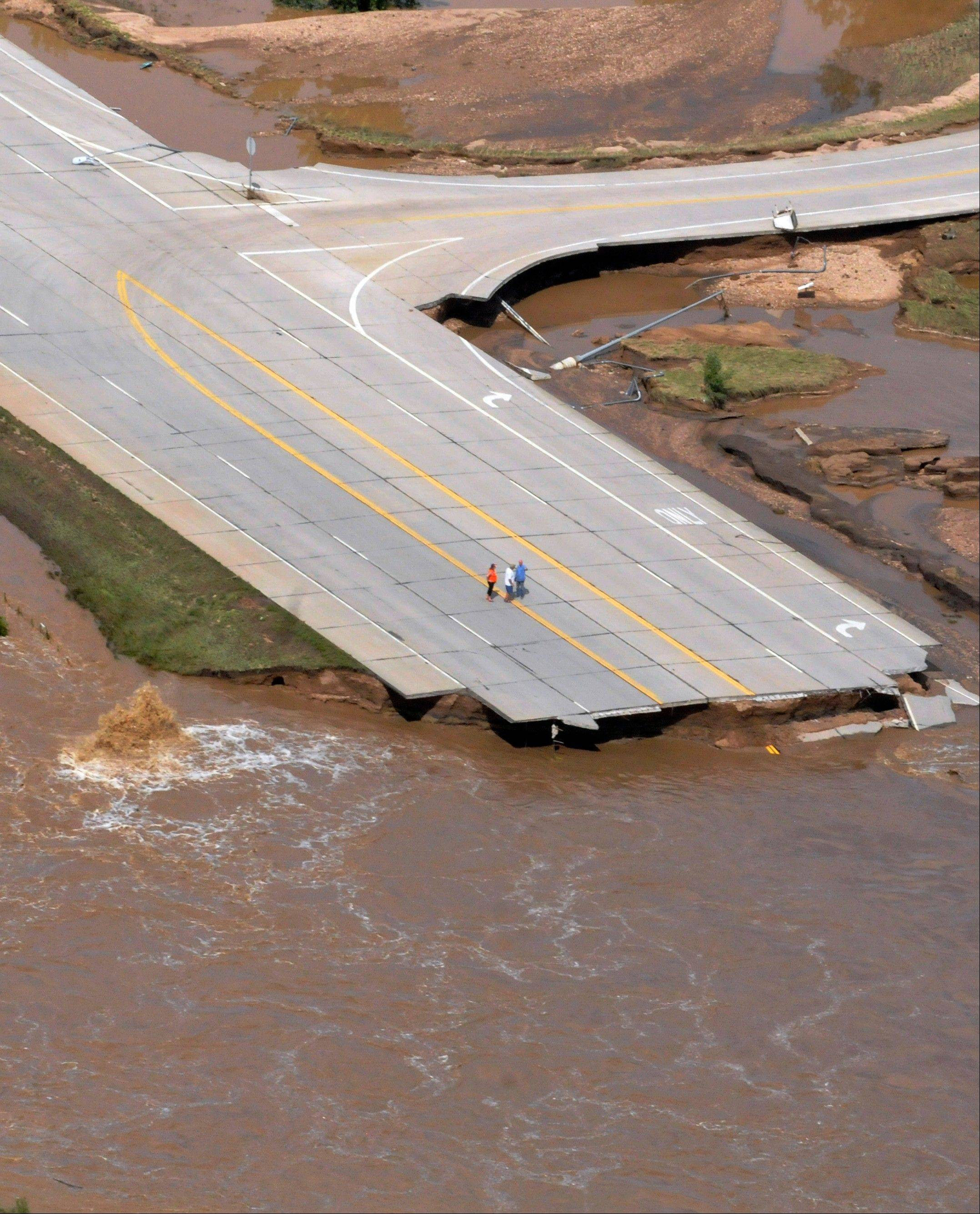A small group of people investigating road damage between Kersey and Greeley, Colo. Four people are confirmed dead and two more are missing and presumed dead after their homes were swept away.