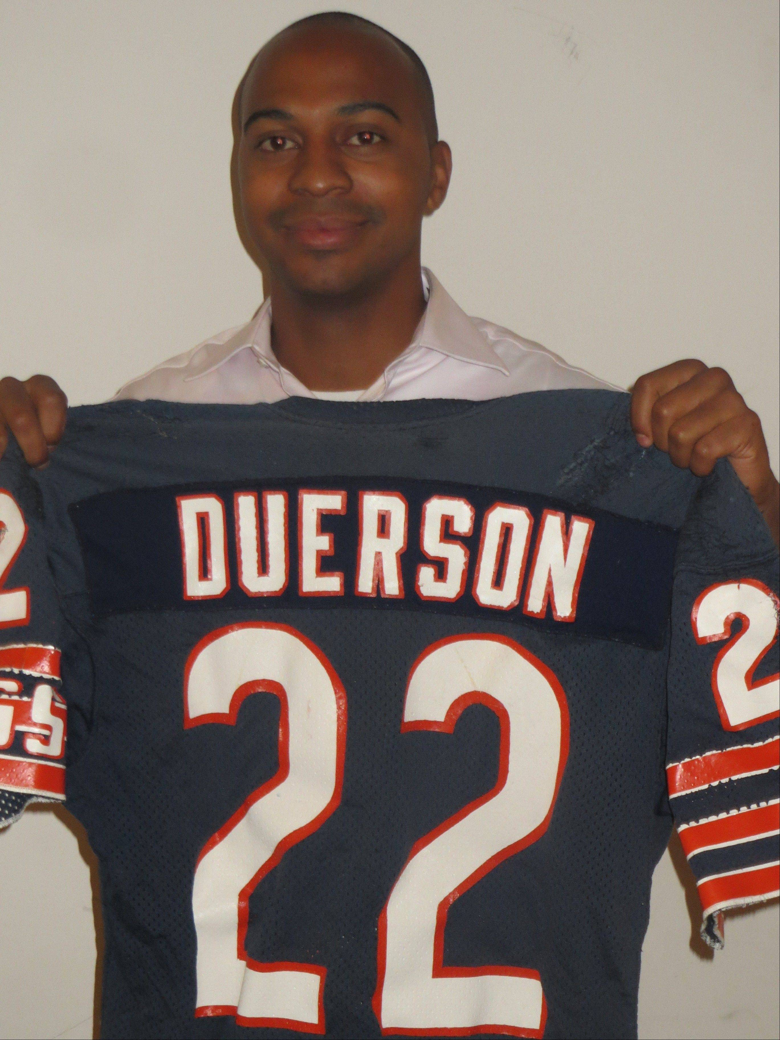 Holding a Bears jersey from his father's playing career, Tregg Duerson honors Dave Duerson's humanitarian legacy by becoming an advocate for suicide prevention.