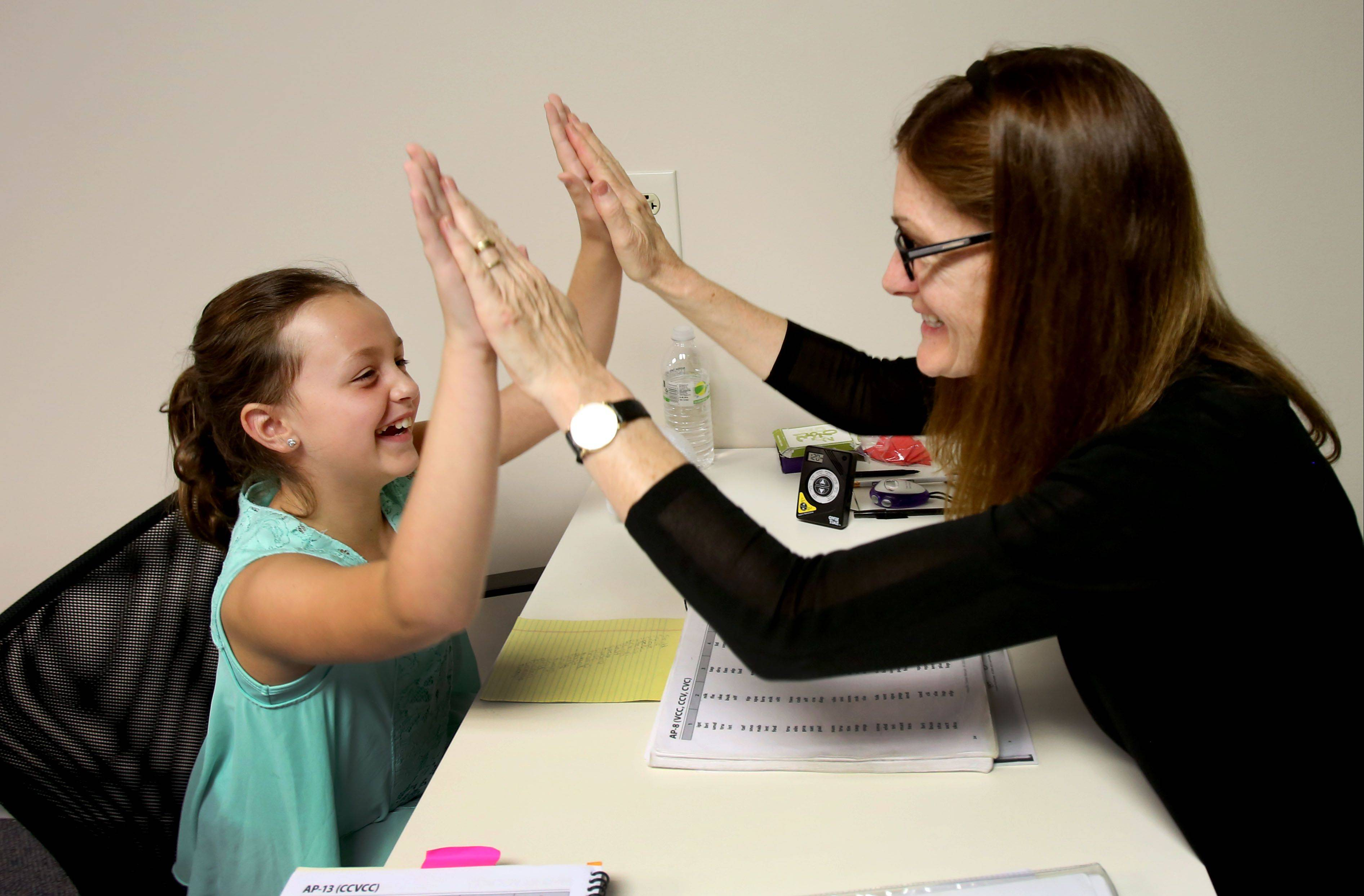 Megan Mason, 9, of Naperville, is congratulated by cognitive brain trainer Becky Lenzi at the LearningRx Chicago-Naperville brain training center. Students receive personalized instruction with the same trainer several times a week to strengthen cognitive skills such as visual and auditory processing, memory and attention.