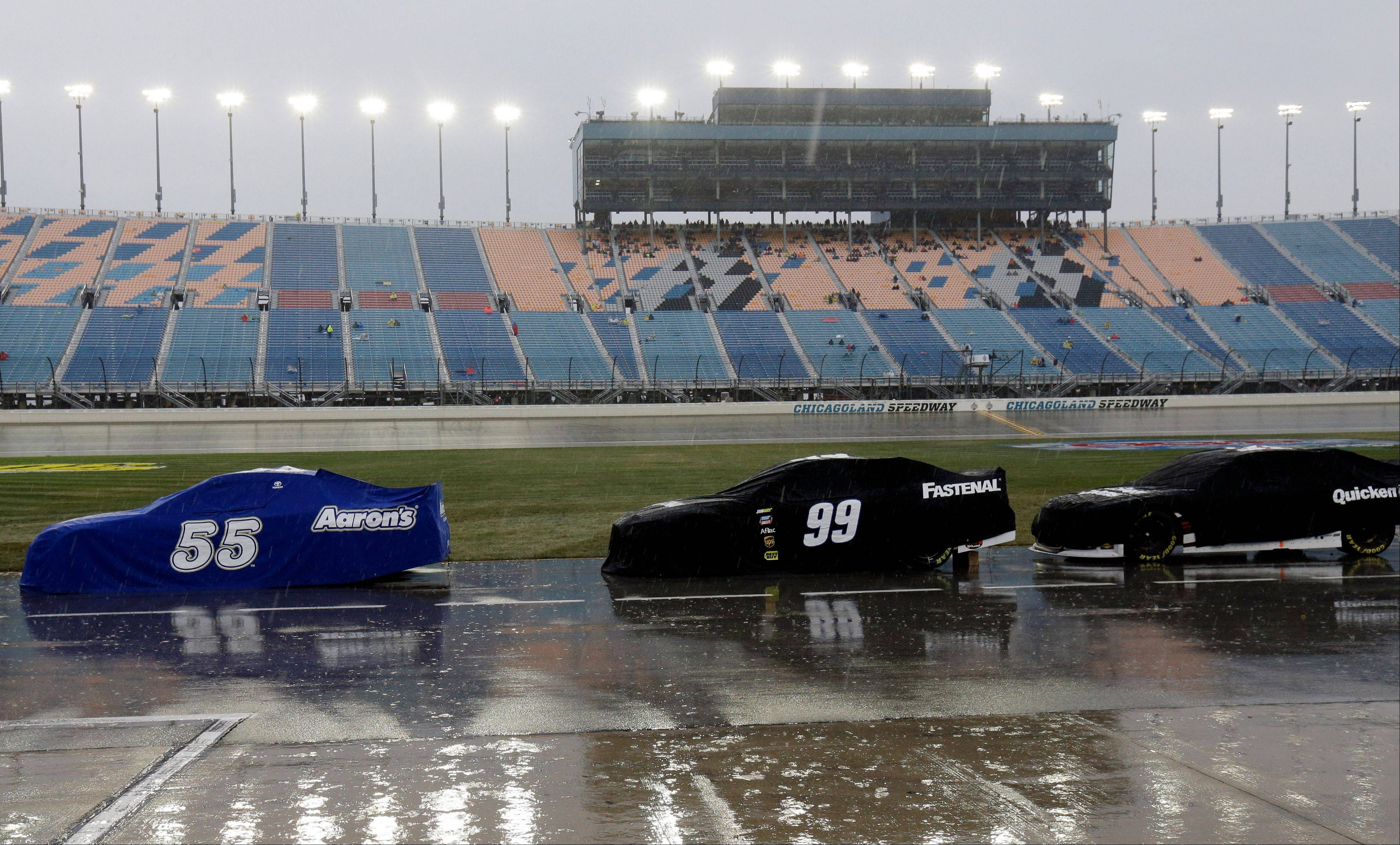 Covered Sprint Cup Series race cars are parked on pit road during rain delay in the NASCAR Sprint Cup series auto race at Chicagoland Speedway in Joliet, Ill., Sunday, Sept. 15, 2013.