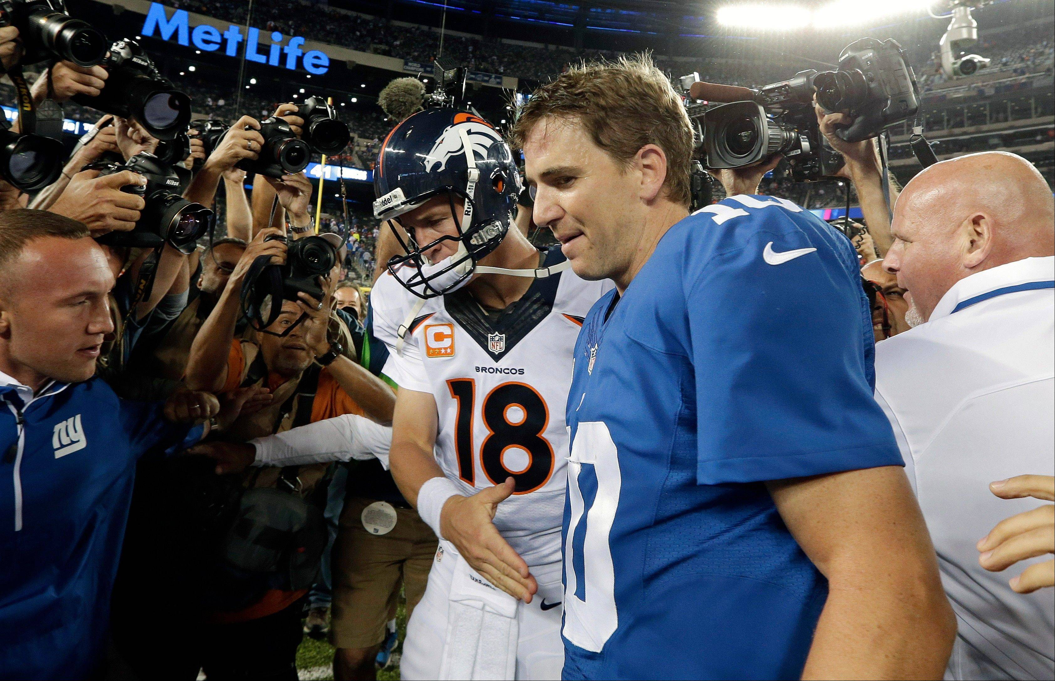 Denver Broncos quarterback Peyton Manning (18) shakes hands with his brother New York Giants' quarterback Eli Manning (10) after an NFL football game Sunday, Sept. 15, 2013, in East Rutherford, N.J. The Broncos won the game 41-23.