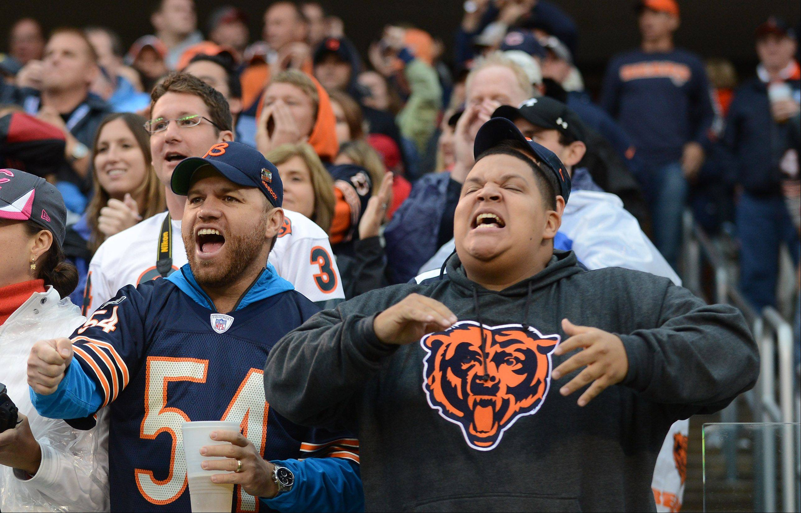 Bears fans try to fire up the defense during Sunday's game at Soldier Field in Chicago.