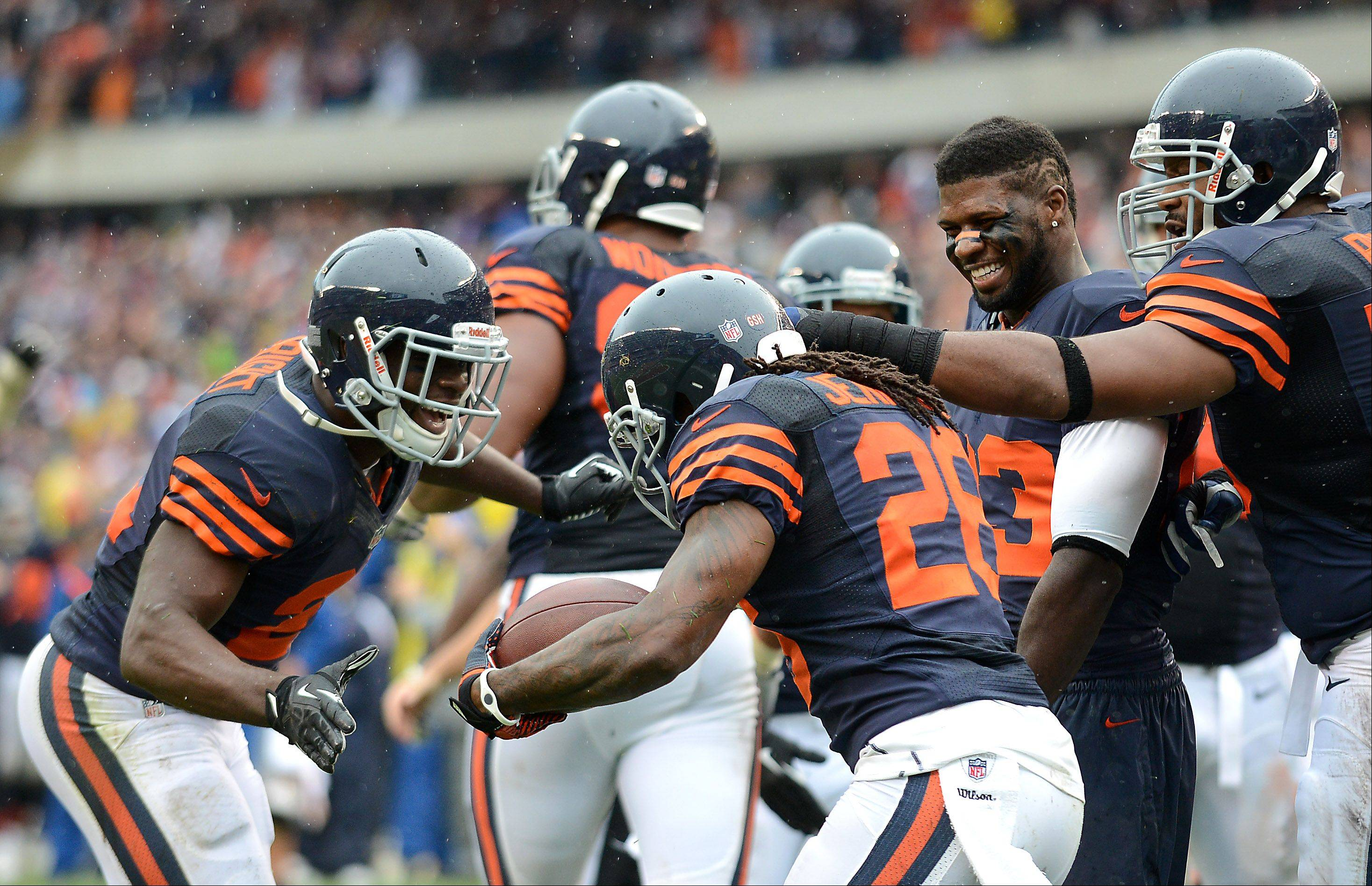 Teammates congratulate Chicago Bears cornerback Tim Jennings (26) after his interception return for a TD during Sunday's game at Soldier Field in Chicago.