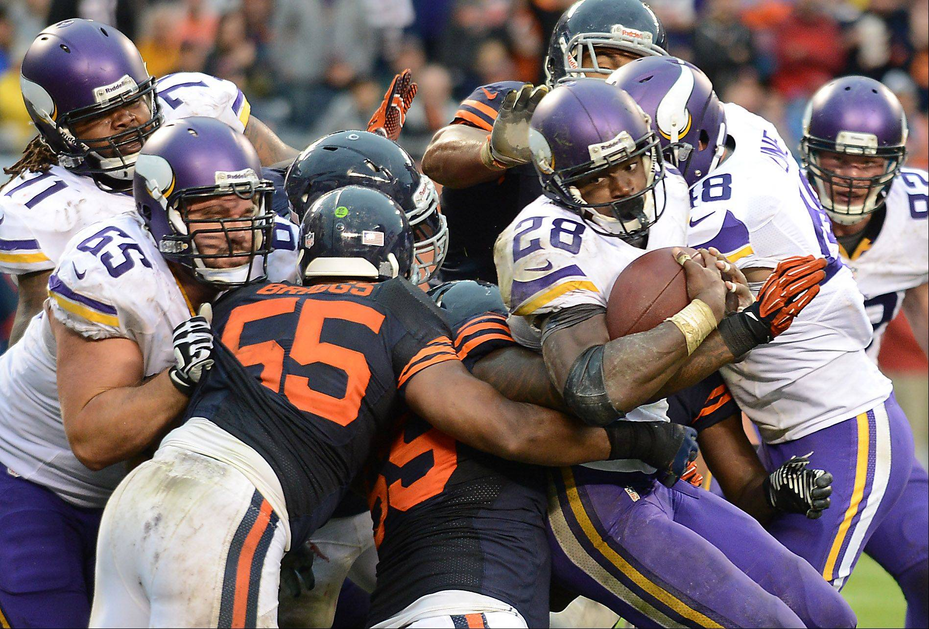 The Bears defense bottles up Minnesota Vikings running back Adrian Peterson (28) on third and short yardage in the fourth quarter during Sunday's game at Soldier Field in Chicago.