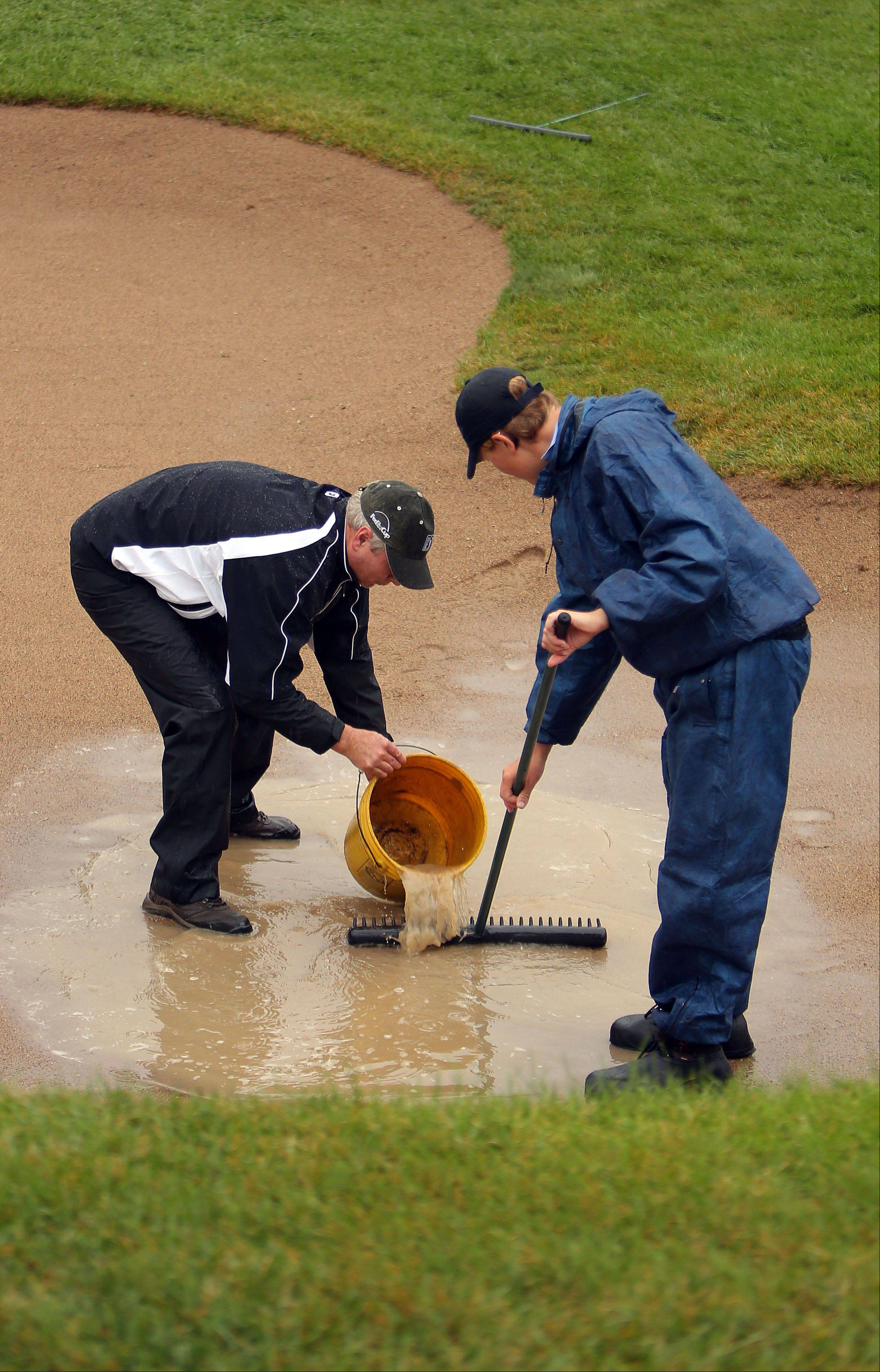Grounds crew try to remove standing water from the bunker on the secondnd hole as rain suspended play during the final round of the BMW Championship on Sunday.