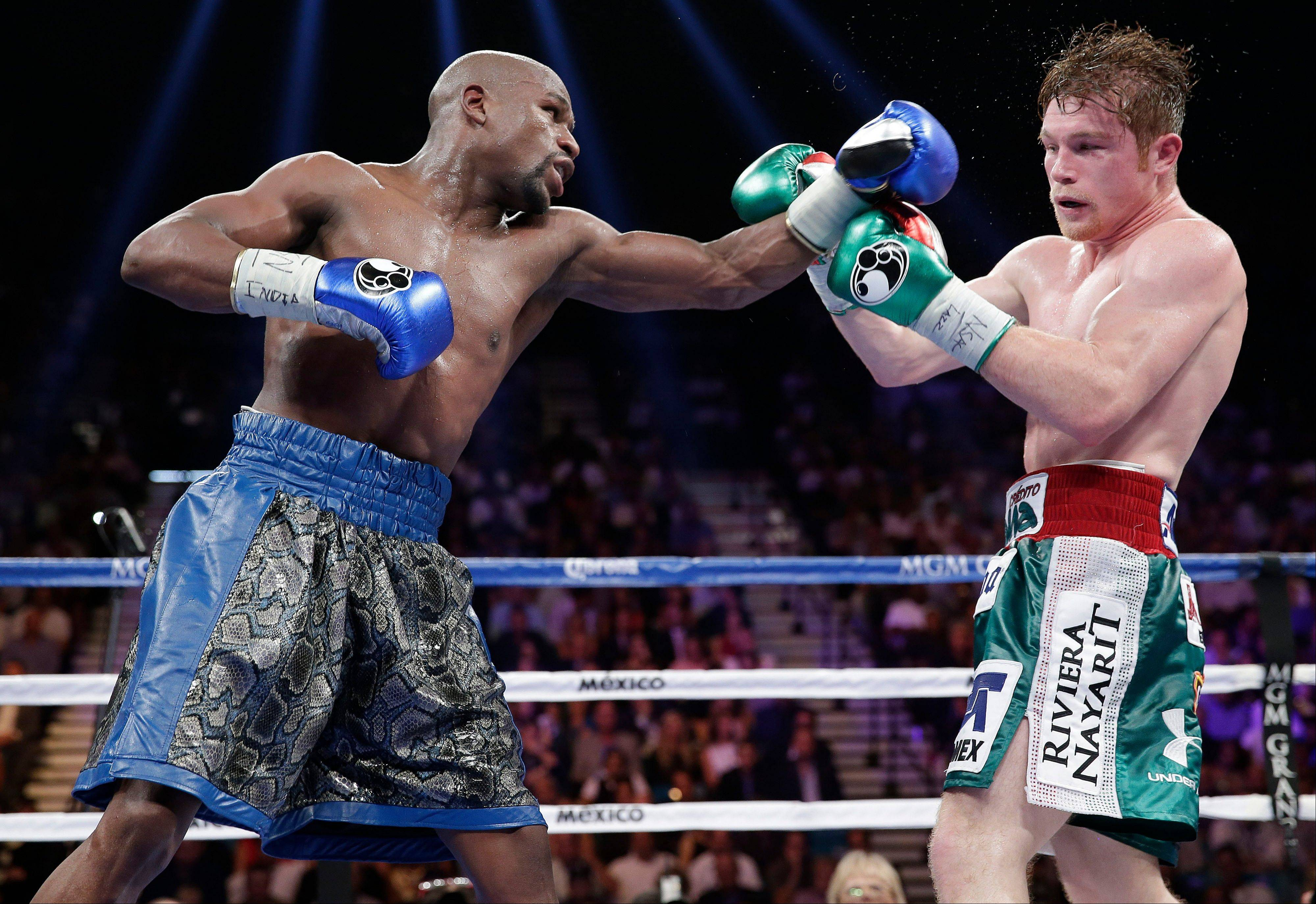 Floyd Mayweather Jr., left, throws a jab against Canelo Alvarez in the 11th round during a 152-pound title fight, Saturday, Sept. 14, 2013, in Las Vegas.