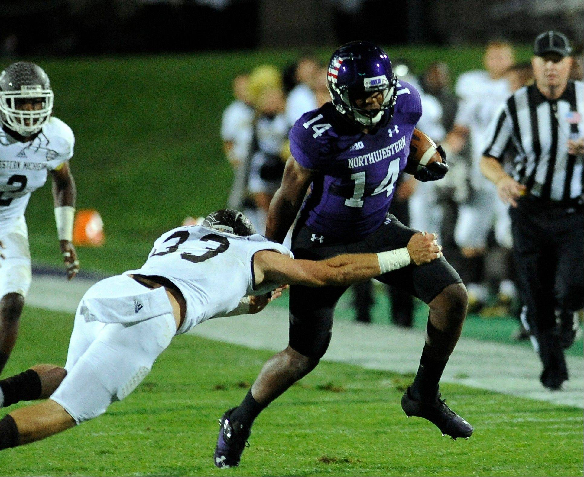 Northwestern's Christian Jones (14) runs against Western Michigan's Justin Currie(33) during the first quarter of an NCAA college football game in Evanston, Ill., Saturday, Sept. 14, 2013.