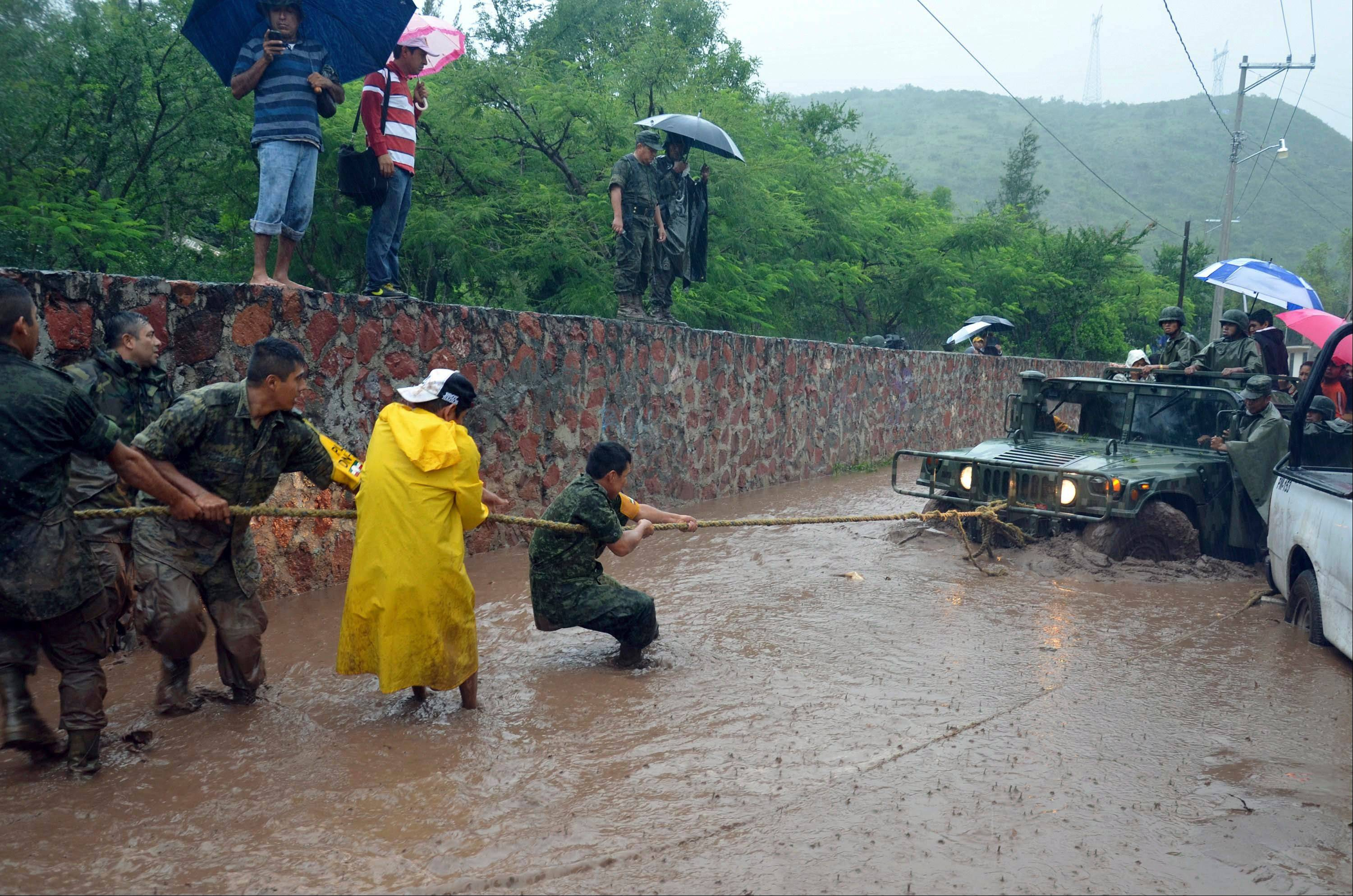 Army soldiers work to try to get their vehicle out of a flooded portion of a road caused by Tropical Storm Manuel in the city of Chilpancingo, Mexico, Sunday. In the southern Pacific Coast state of Guerrero, rains unleashed by Manuel resulted in the deaths of six people when their SUV lost control on a highway headed for the tourist resort of Acapulco. Another five people died in landslides in Guerrero and Puebla states, while the collapse of a fence killed another person in Acapulco.
