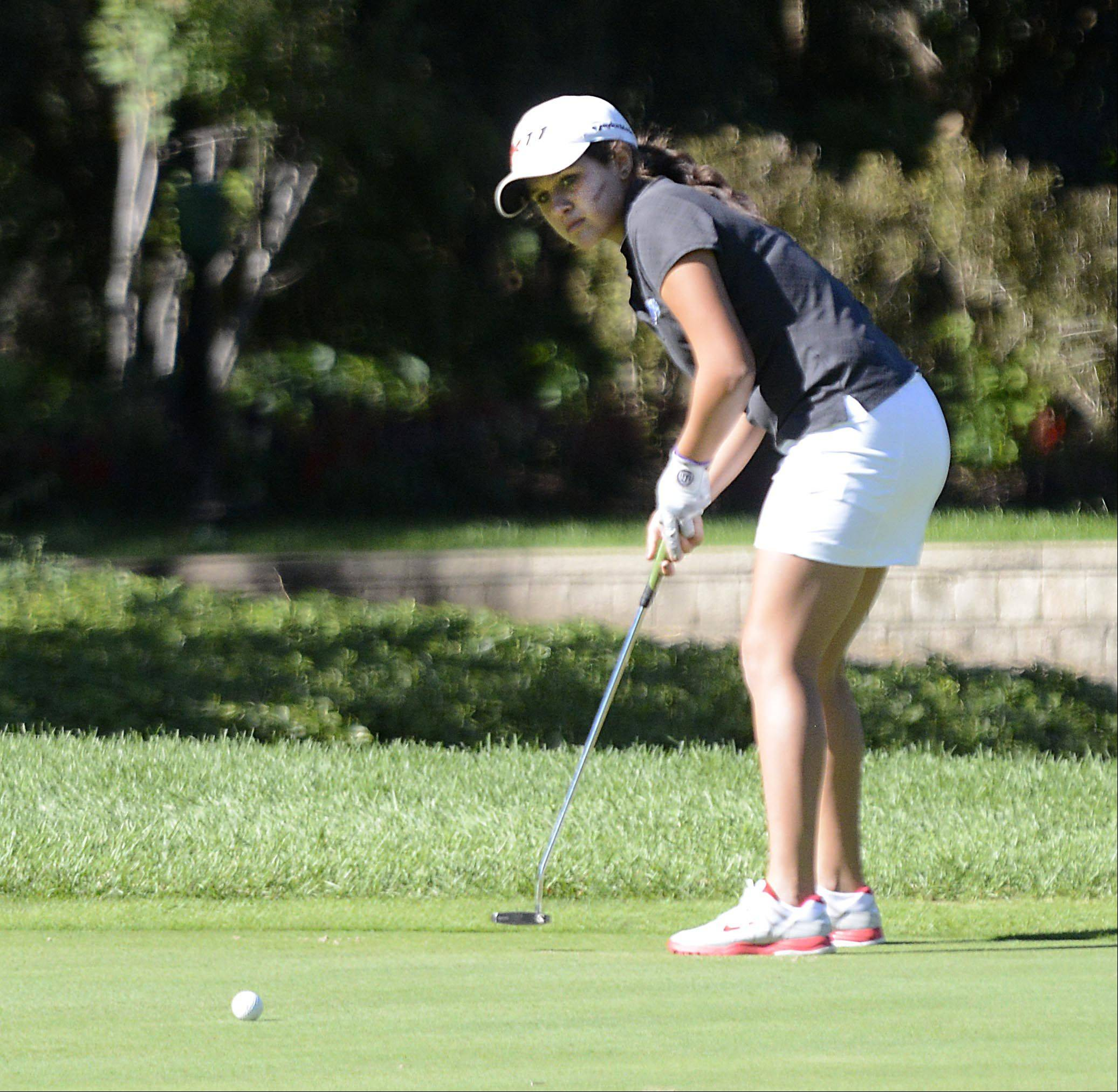 St. Charles North�s Gianna Furrie watches her long putt on No. 8 Monday at the Elgin Country Club girls golf invitational. Furrie won the individual title with a 3-over par 38.