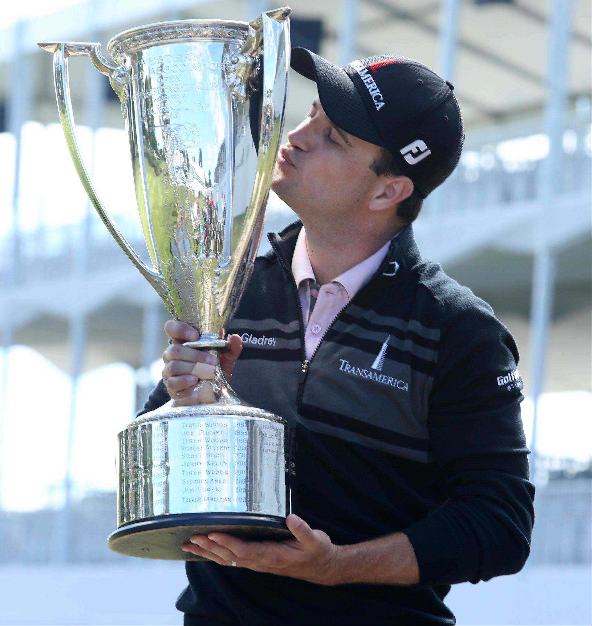 Zach Johnson kisses the J.K. Wadley Trophy after winning the BMW Championship at Conway Farms Golf Club in Lake Forest on Monday.