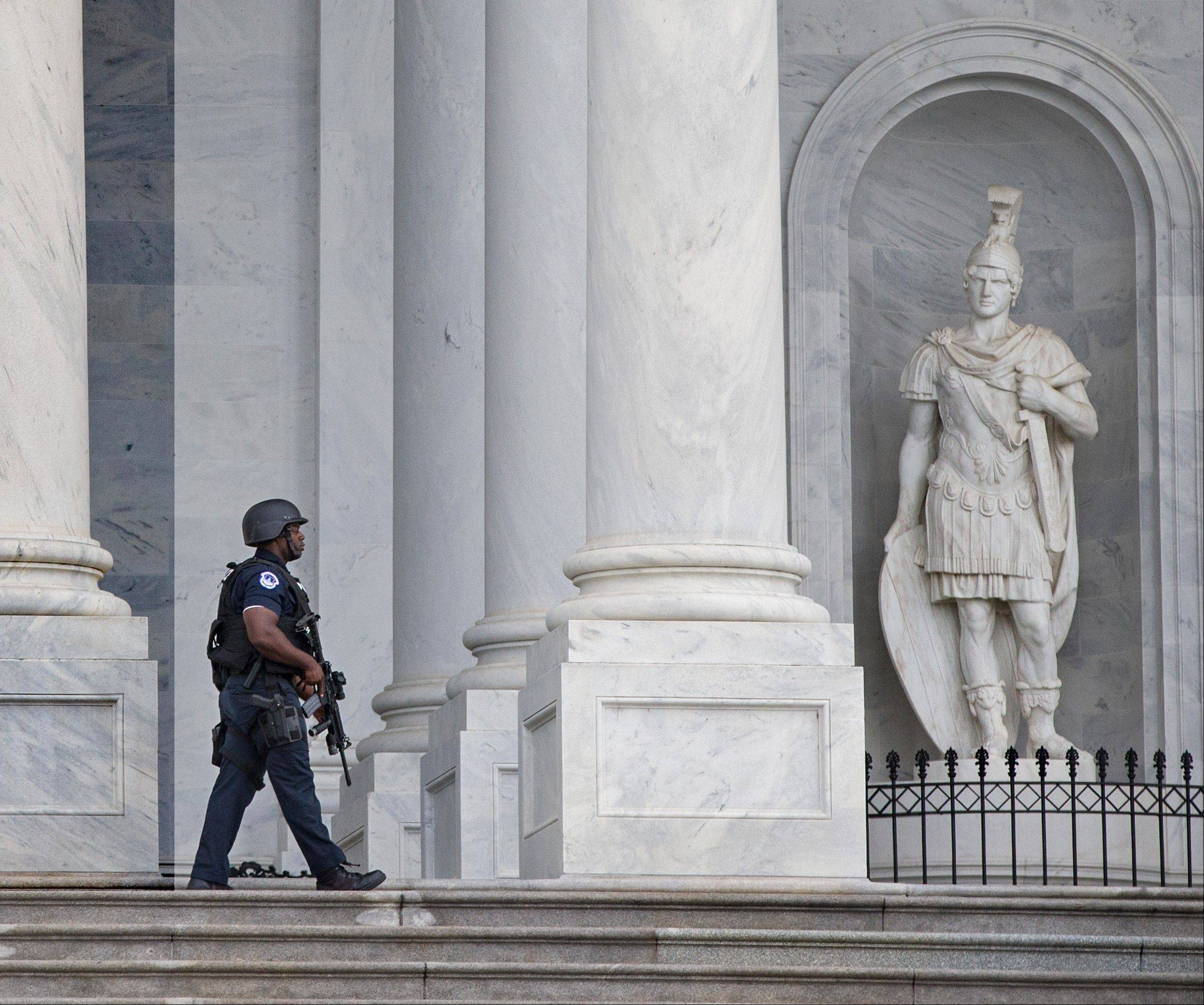 A U.S. Capitol Police officer patrols the steps at the Capitol as the investigation continues at the nearby Washington Navy Yard where at least one gunman opened fire Monday in Washington.