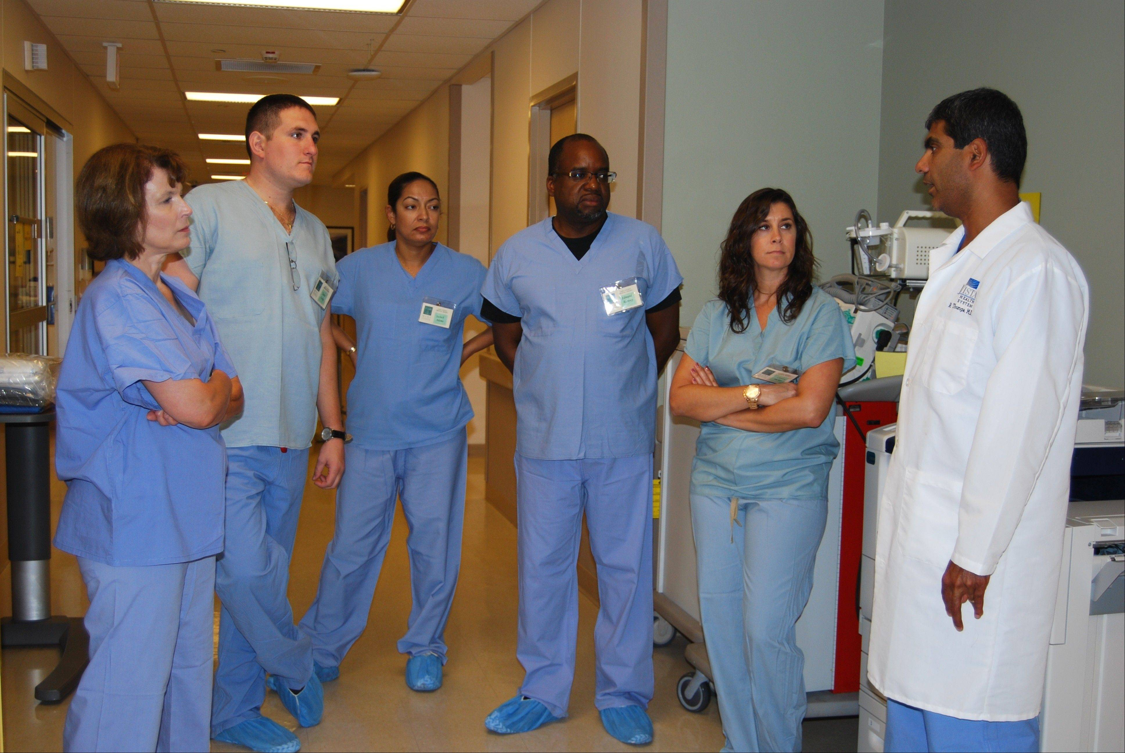 Participants of the 2013 Class of Mini Interns talk with Dr. Raghu Thunga in the ICU at Vista Medical Center East.